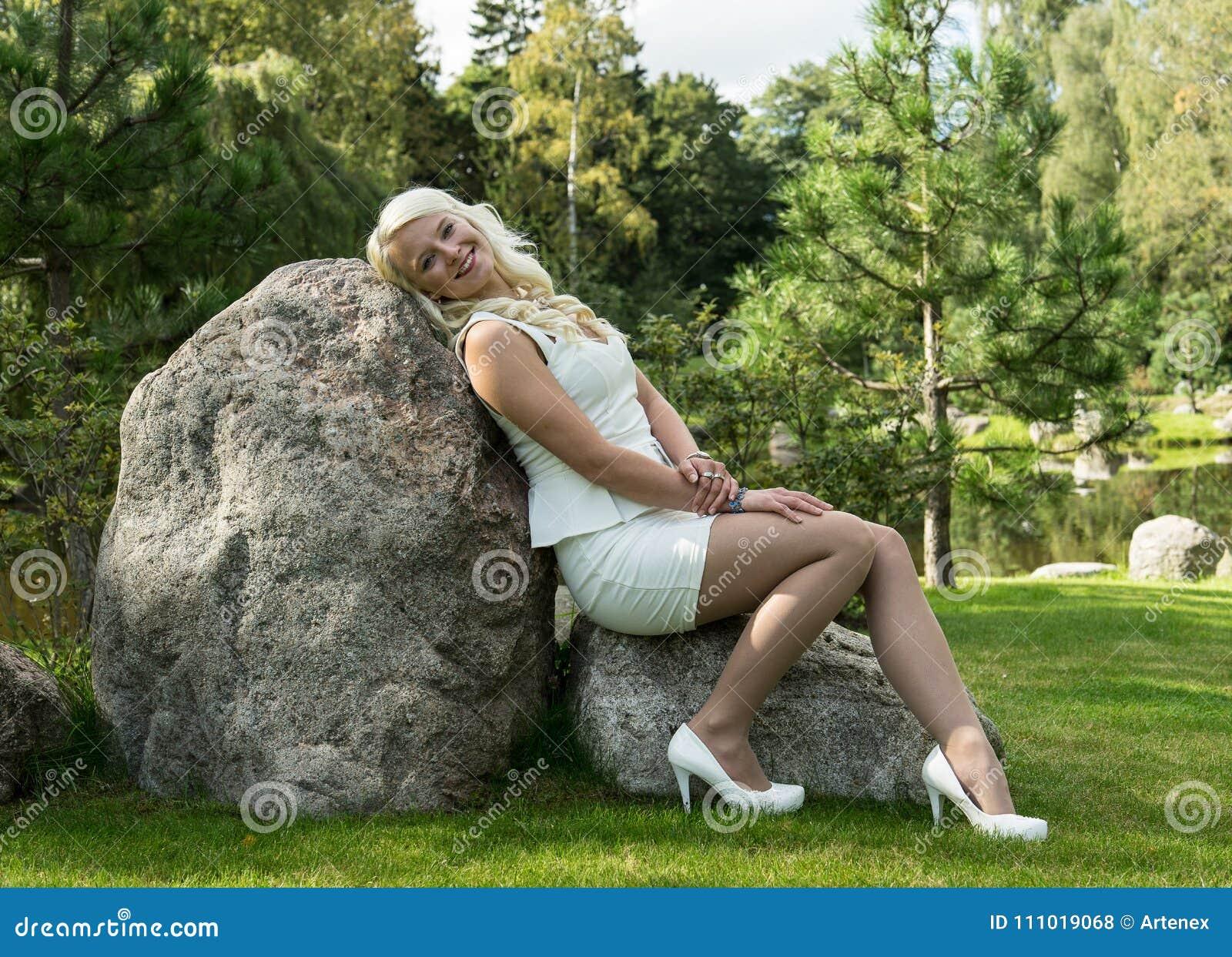 Mujer rubia que se sienta en una piedra Chica joven que descansa en naturaleza