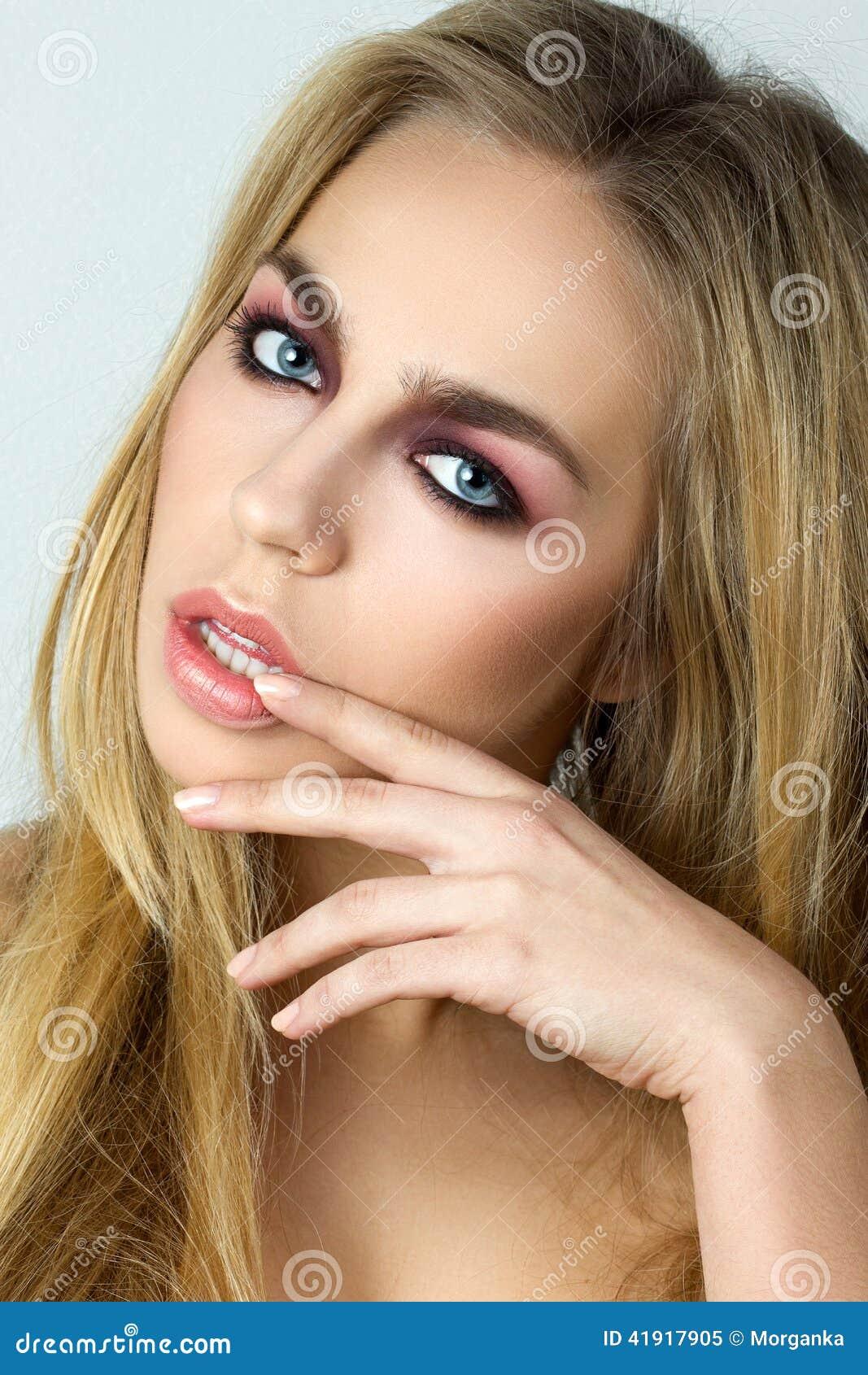 Mujer rubia que toca sus labios