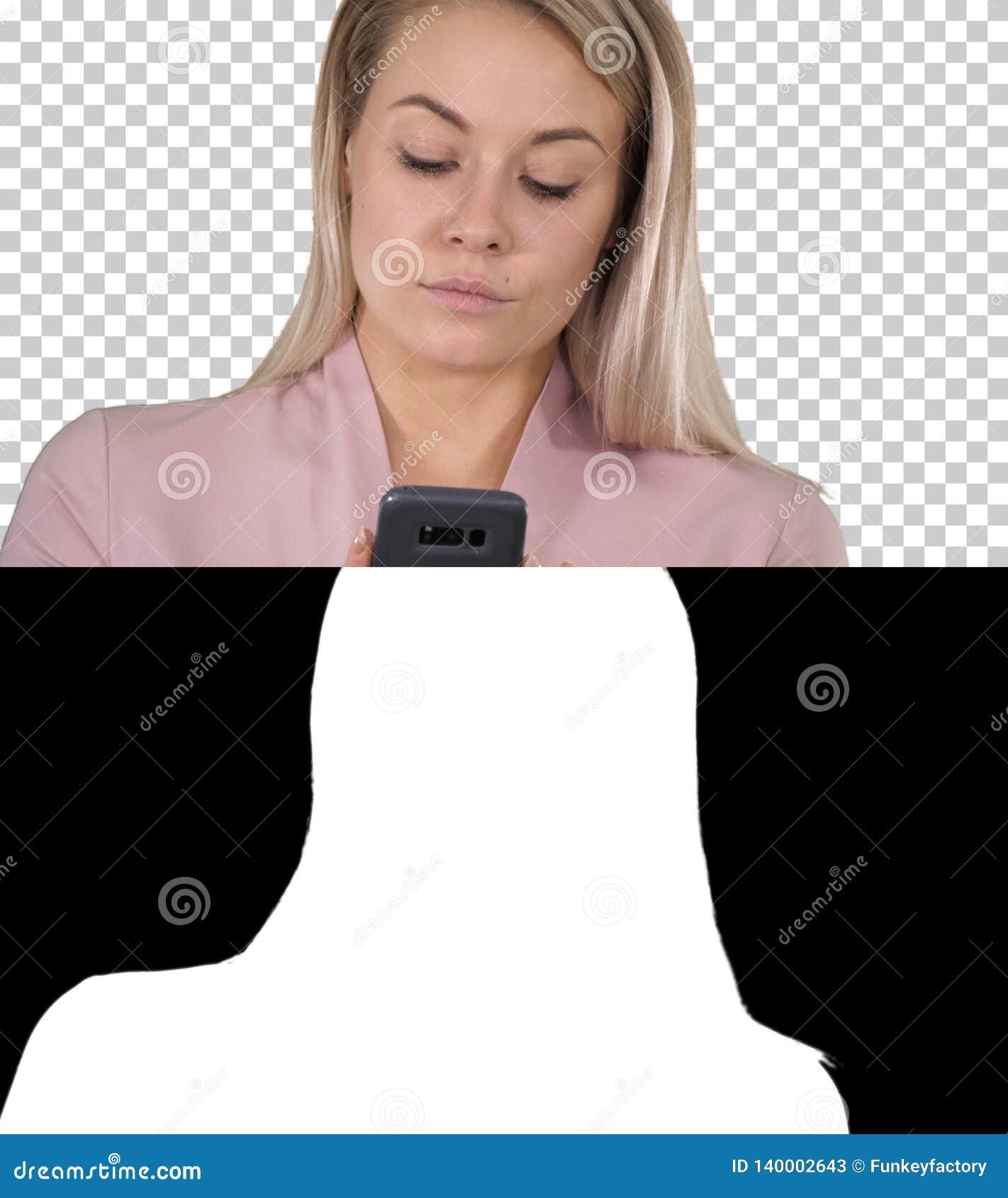 Mujer rubia sonriente de moda que usa su teléfono móvil que sonríe como ella mecanografía un mensaje de texto, Alpha Channel