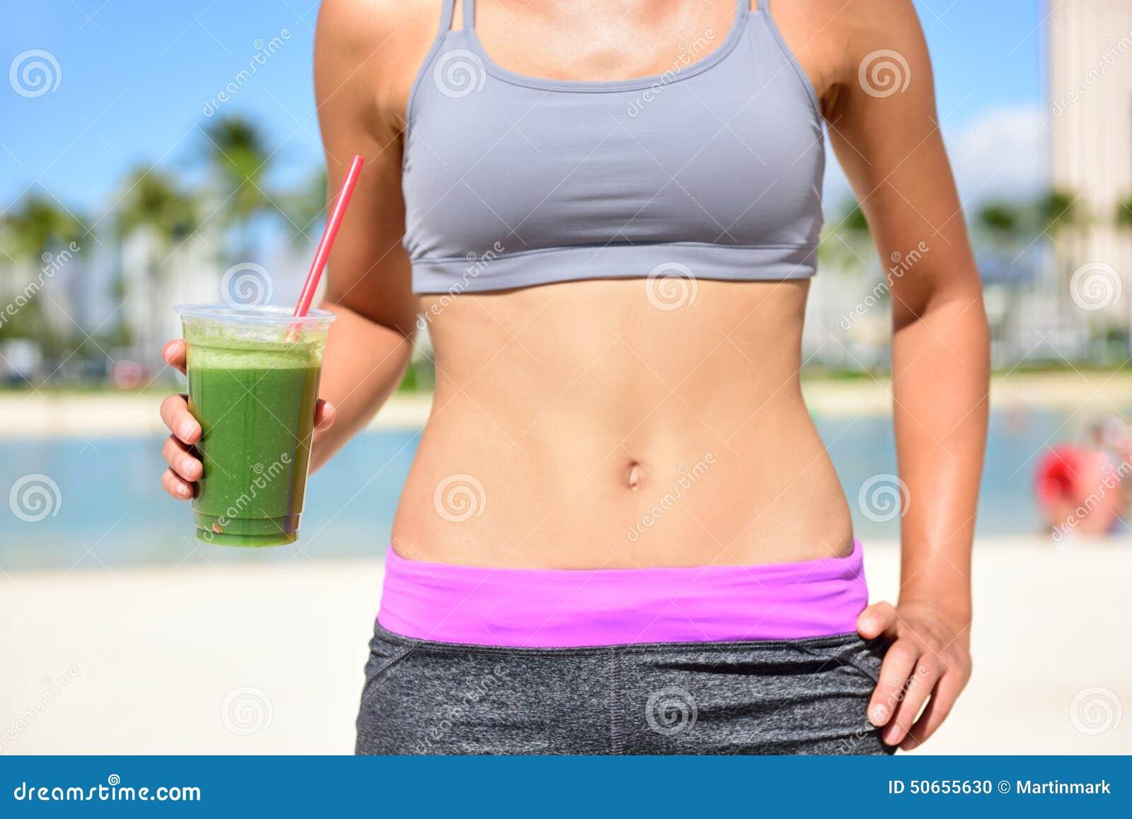 Mujer sana de la forma de vida que bebe el smoothie verde
