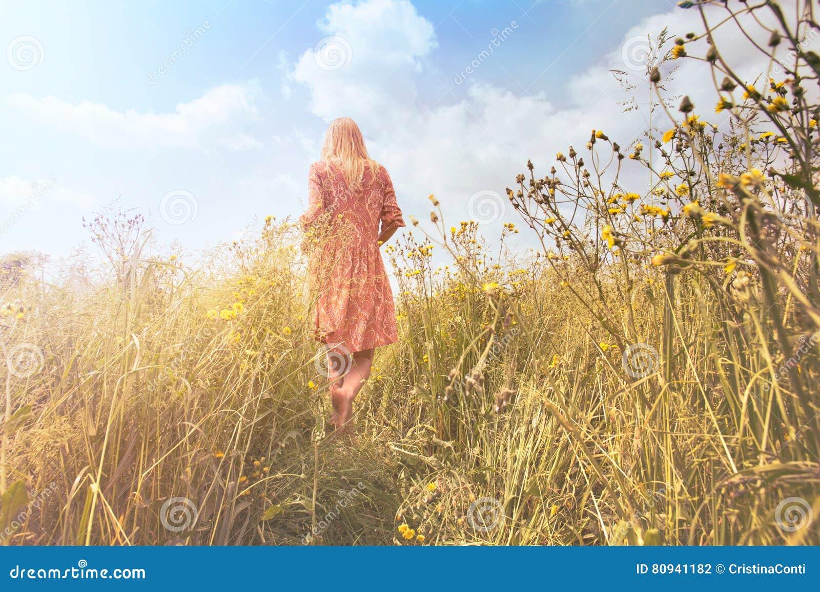 Mujer soñadora que camina en naturaleza hacia el sol