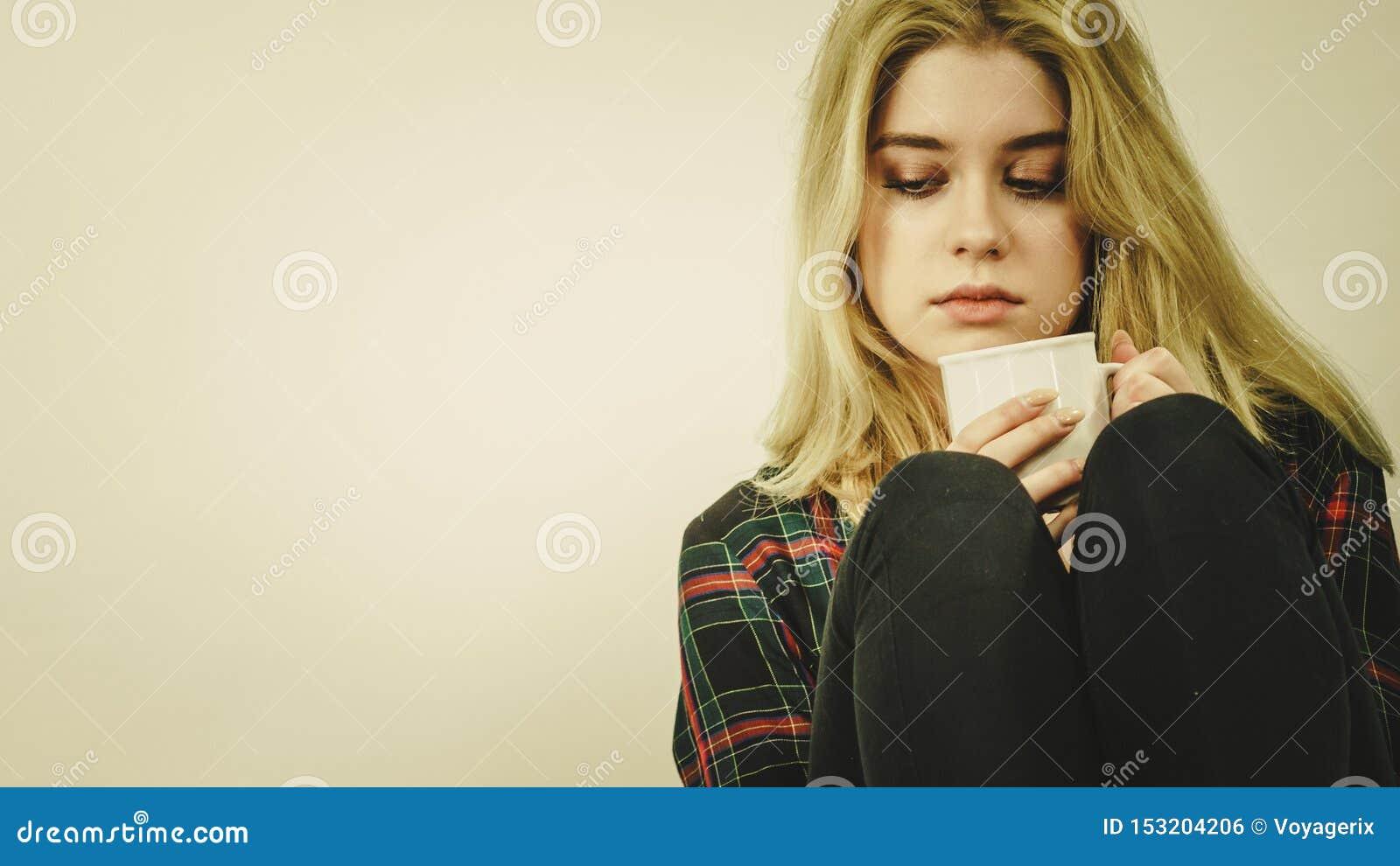 Mujer sola triste que se sienta en el sof? con la taza