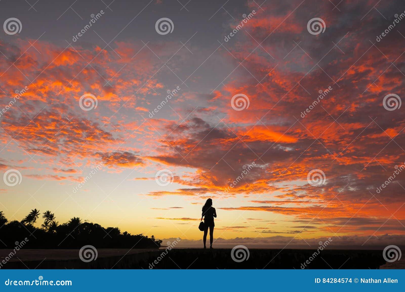 Mujer a solas del viajero y puesta del sol increíble de la isla