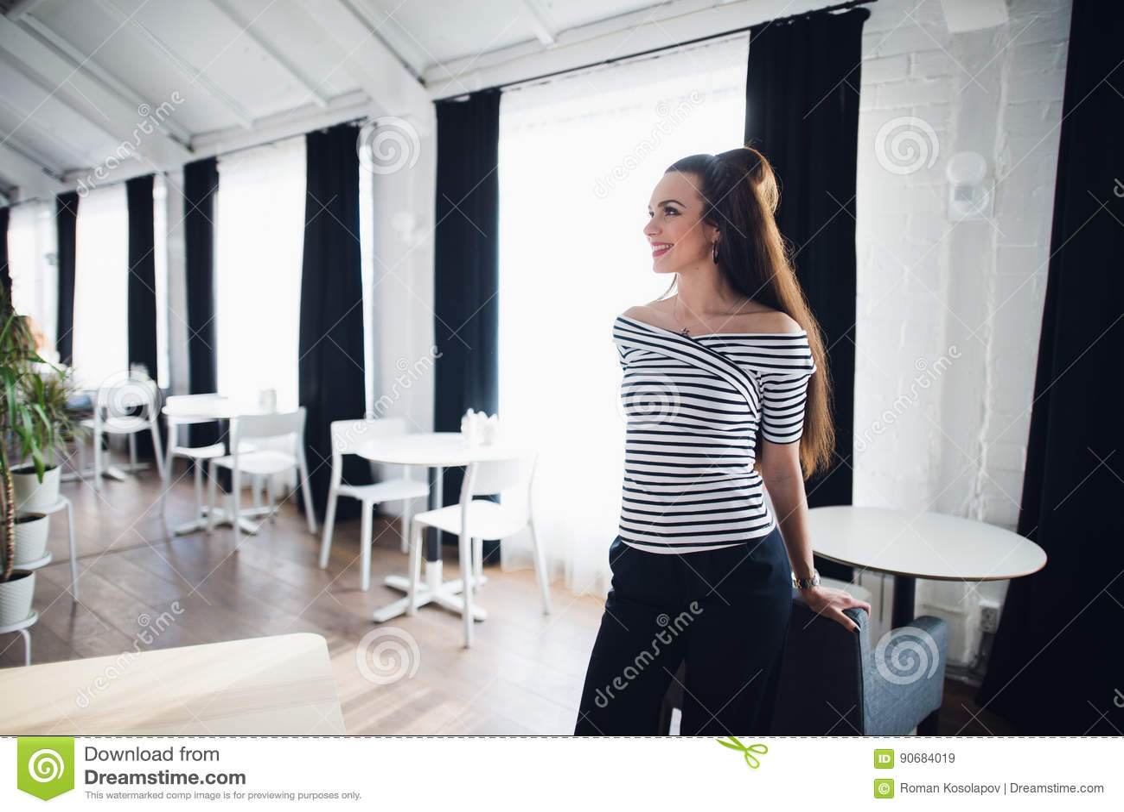 Mujer sonriente amistosa del retrato que sueña o que piensa en un estudio Mujer de mediana edad bien arreglada hermosa en casa