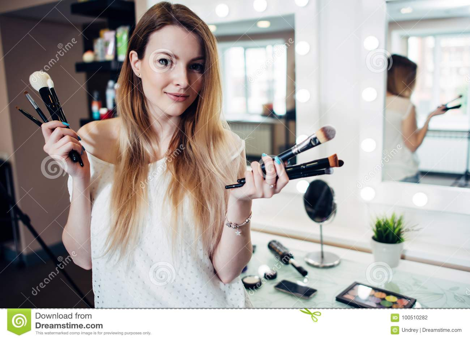 Mujer sonriente bonita que se coloca con una variedad de cepillos del maquillaje en el estudio de la belleza