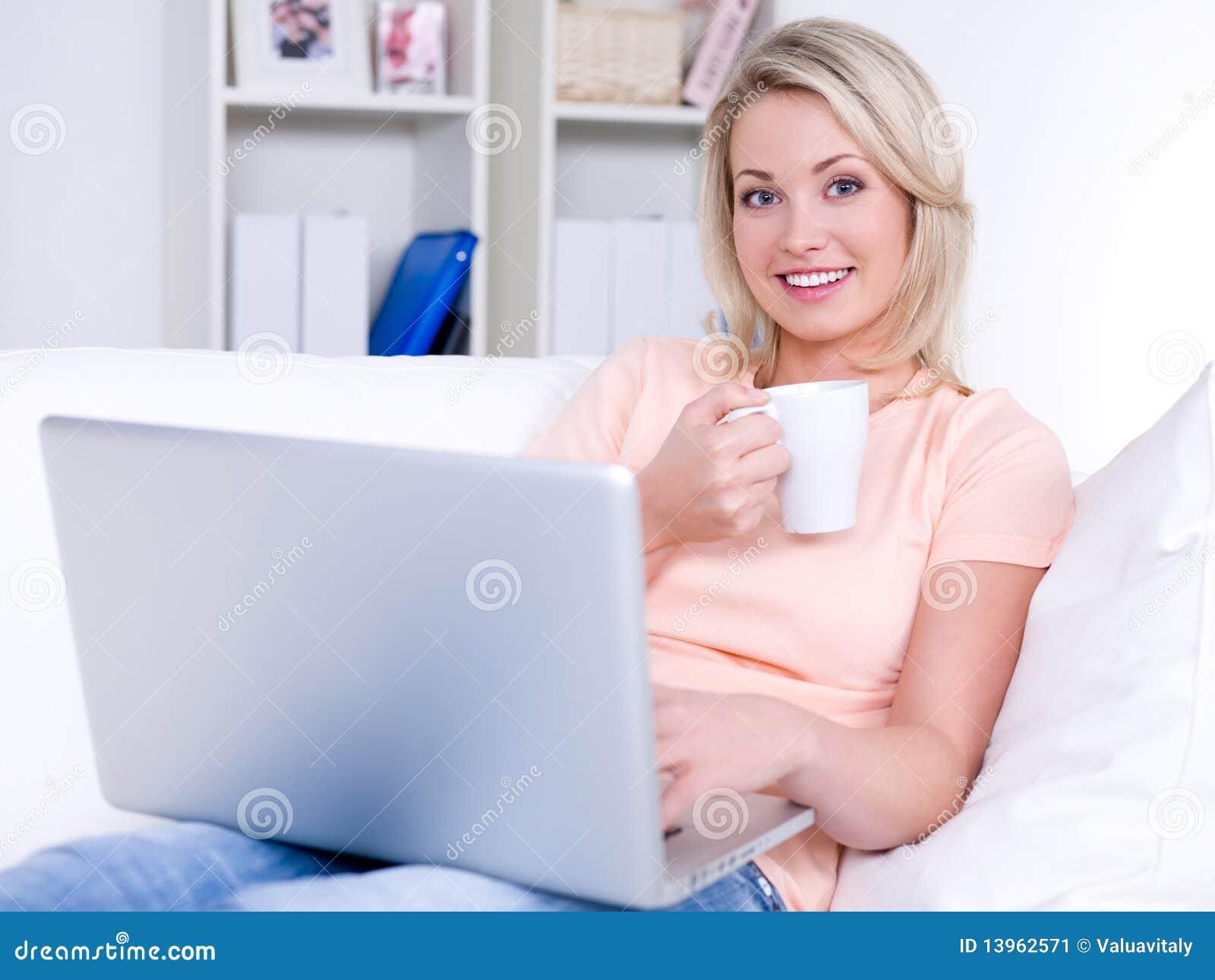 Mujer sonriente con la computadora portátil y la taza de café