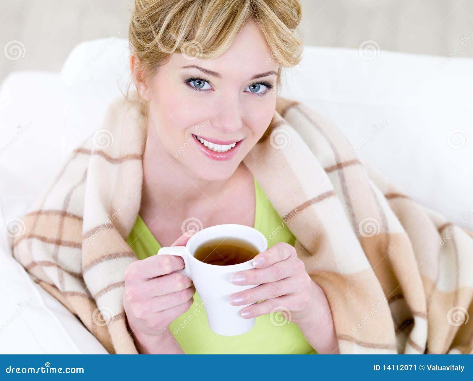 Mujer sonriente con la taza de café caliente