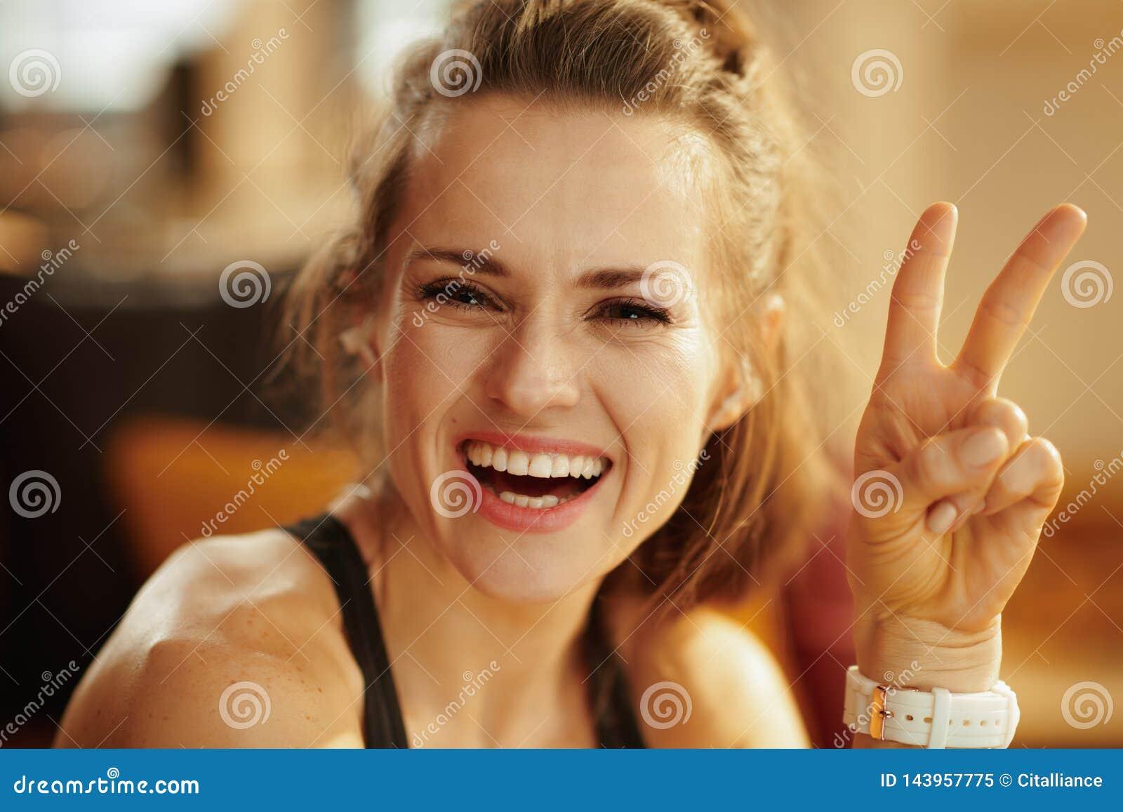 Mujer sonriente de los deportes en la victoria moderna de la demostración de la sala de estar