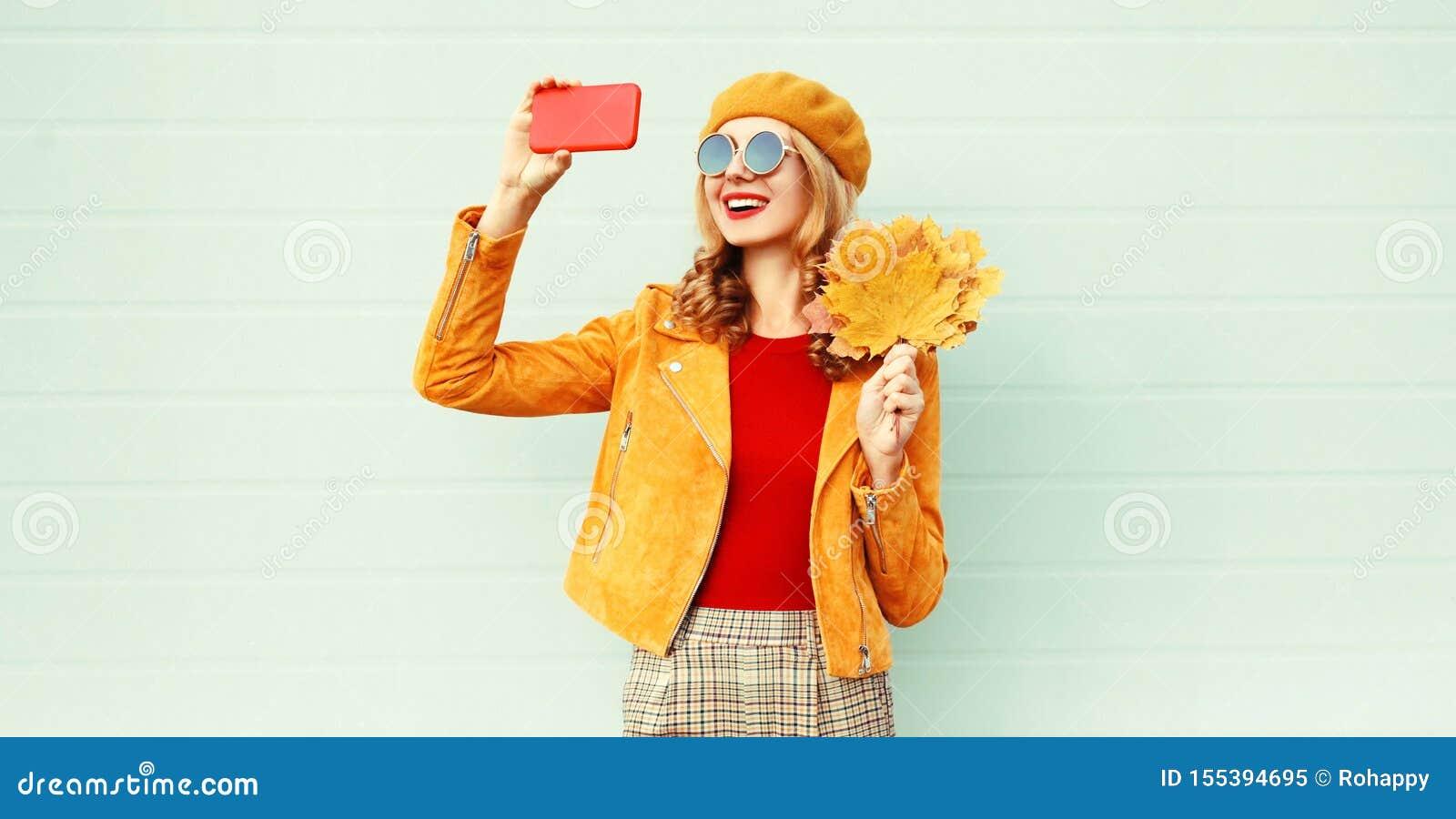 Mujer sonriente del otoño que toma la imagen del selfie por el teléfono que sostiene las hojas de arce amarillas que llevan el so