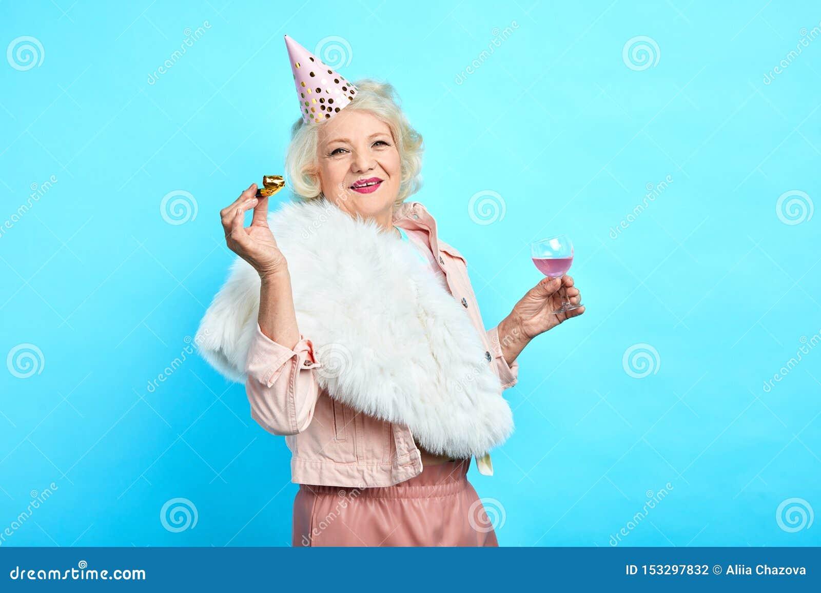 Mujer sonriente elegante en la ropa de moda que se divierte en su cumpleaños