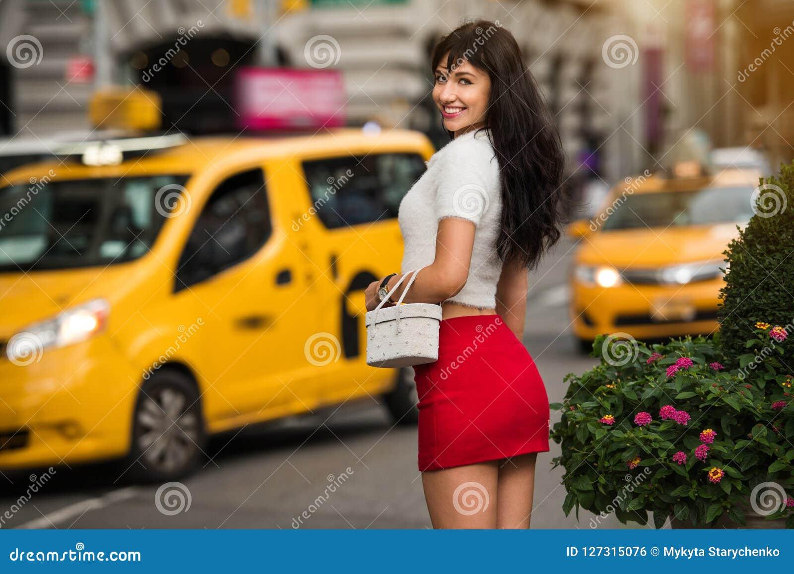 Mujer sonriente elegante hermosa que camina para amarillear el taxi en la calle de la ciudad de Nueva York