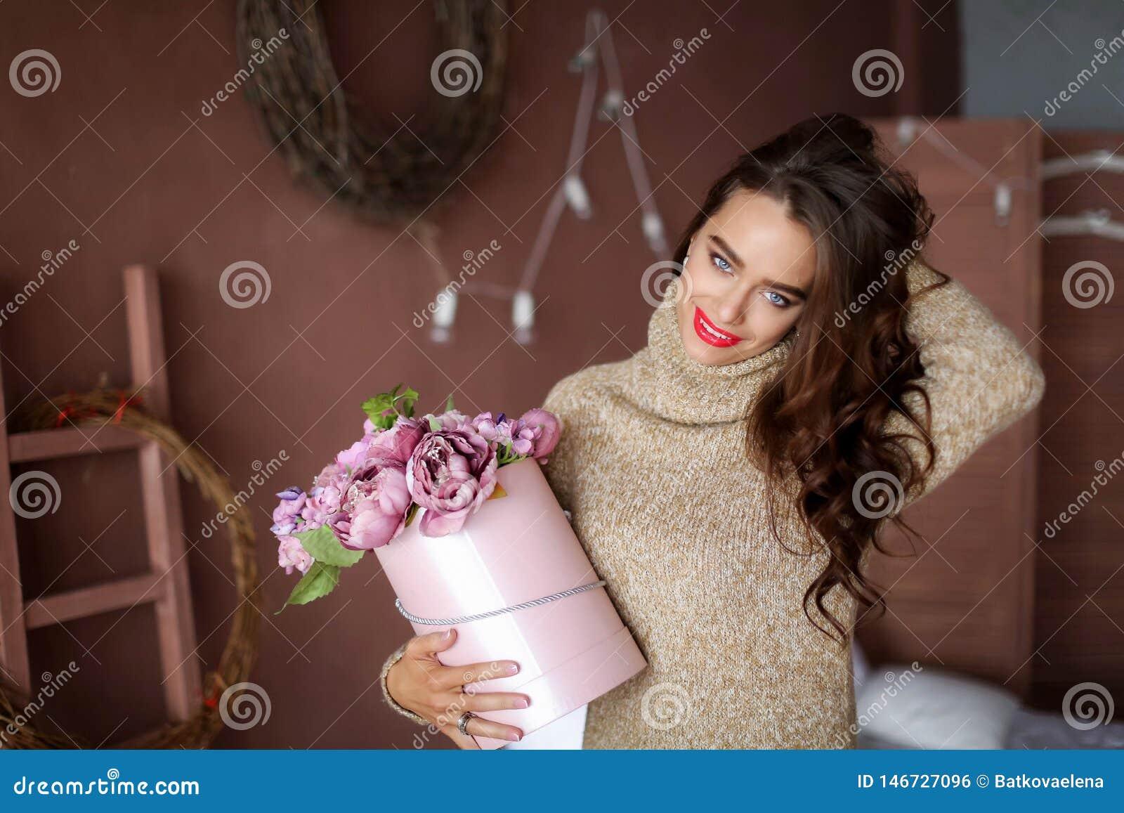 Mujer sonriente en caja de regalo de la tenencia del pijama y mirada de la c?mara, concepto de d?a de San Valent?n
