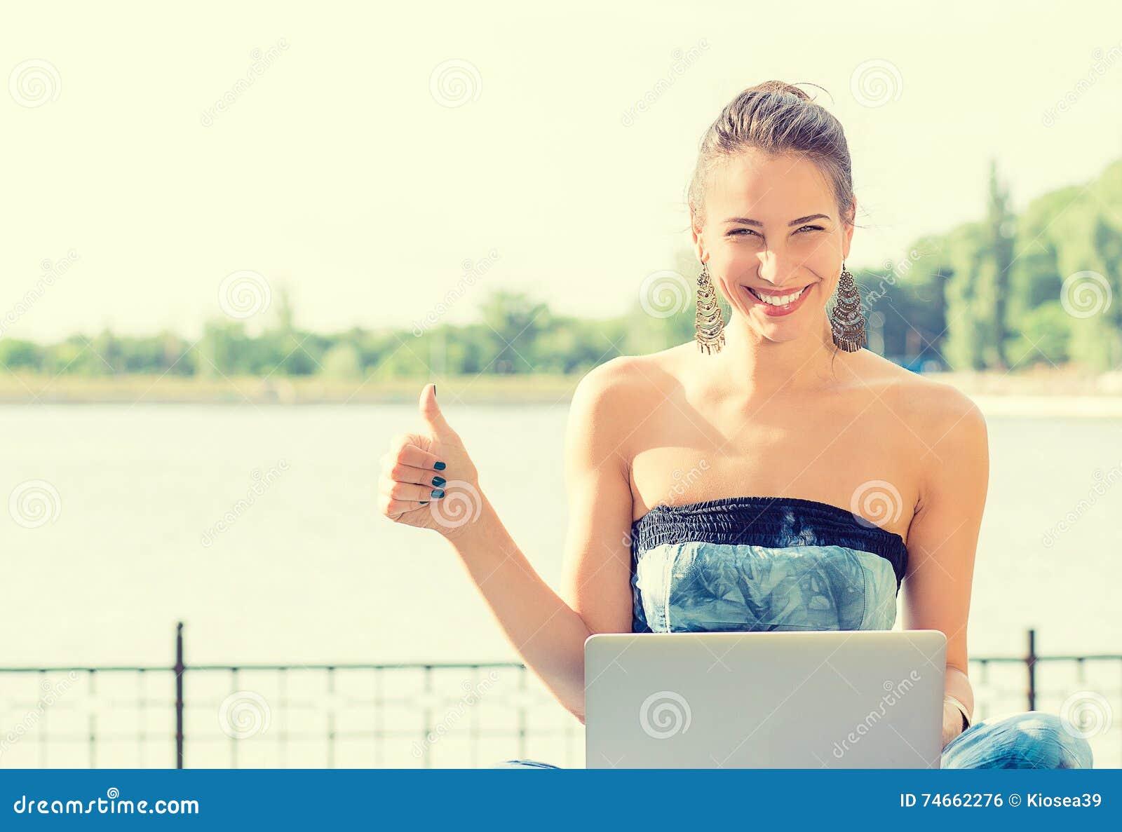 Mujer sonriente en la playa que se sienta en hierba con el ordenador