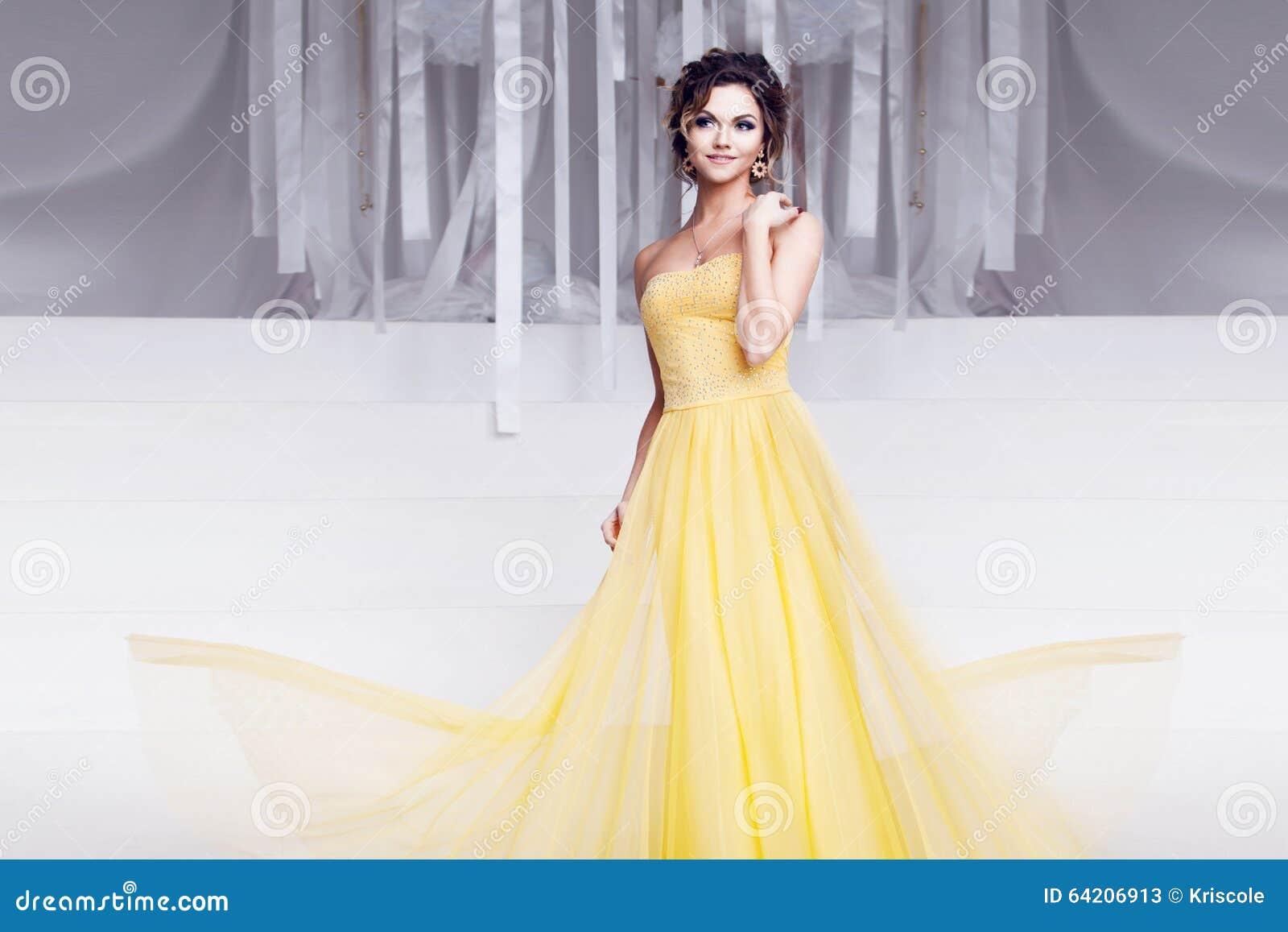 Mujer sonriente en vestido de noche amarillo y con