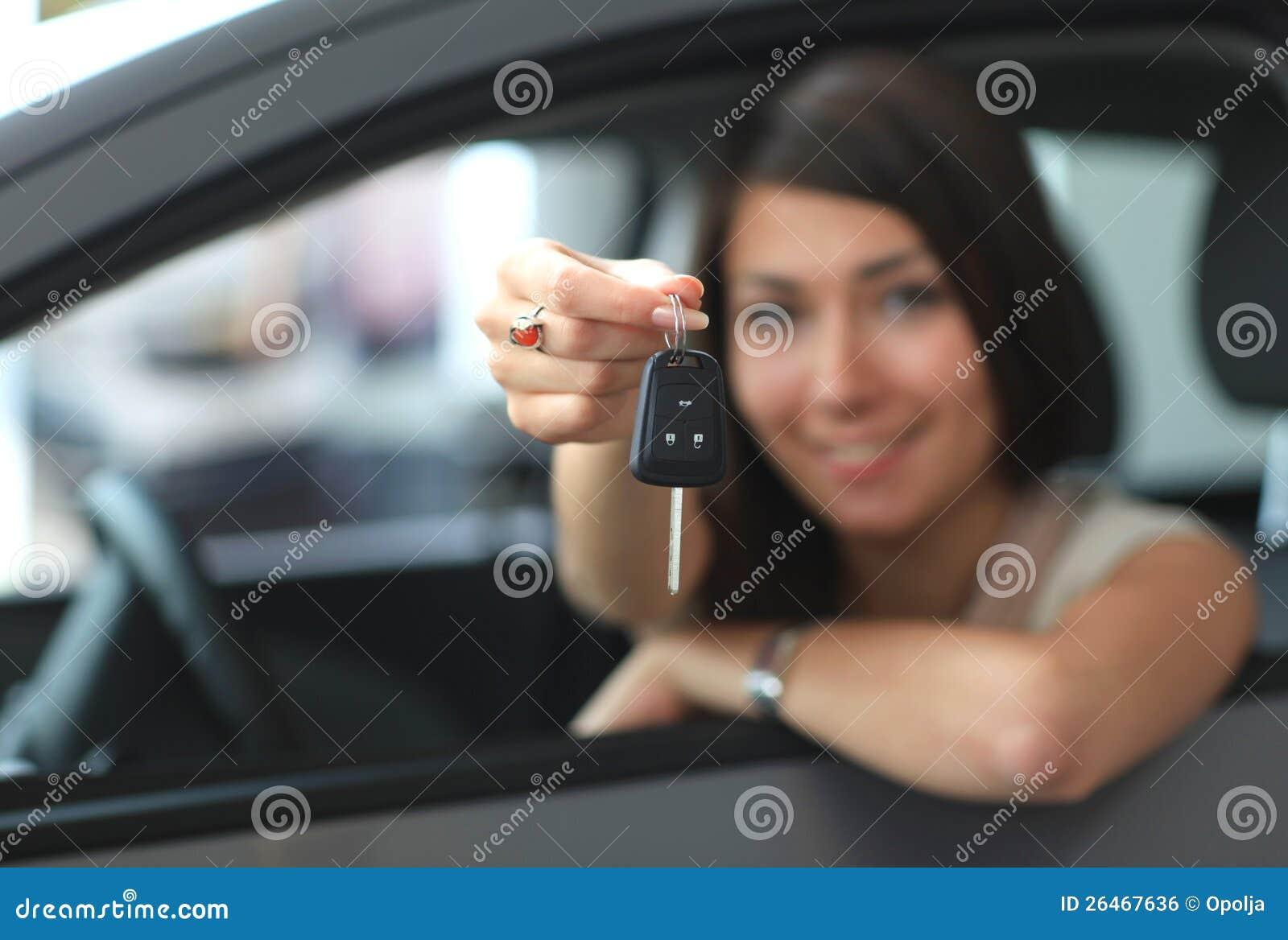 Mujer sonriente feliz con clave del coche