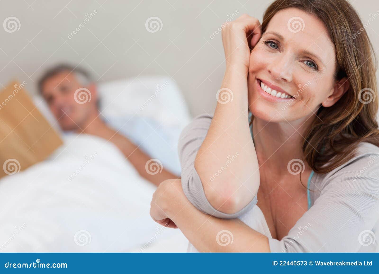 Mujer sonriente feliz en cama con la lectura del marido detrás de ella