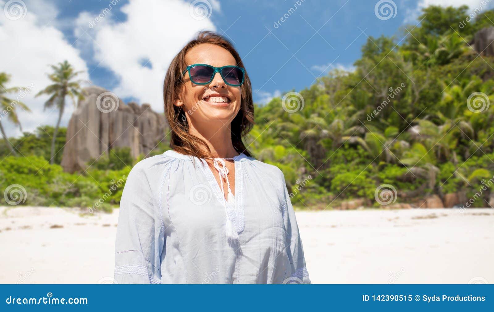 Mujer sonriente feliz en gafas de sol sobre la playa