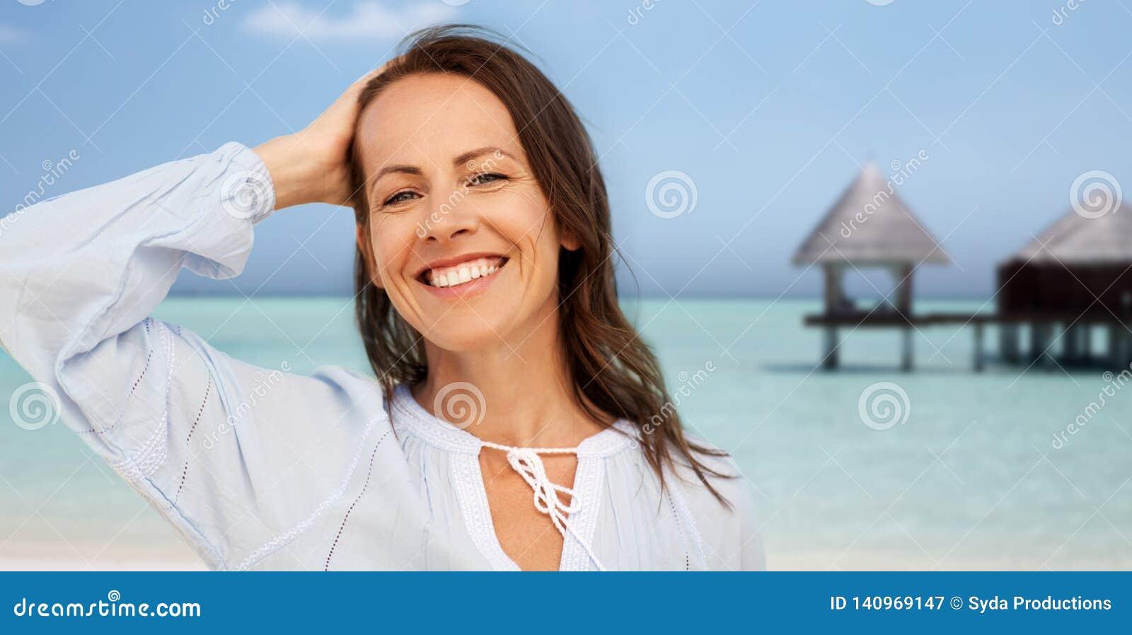 Mujer sonriente feliz en la playa del verano