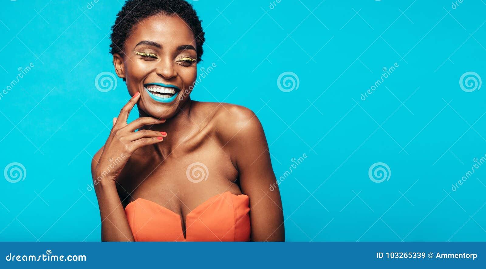 Mujer sonriente hermosa con maquillaje vivo