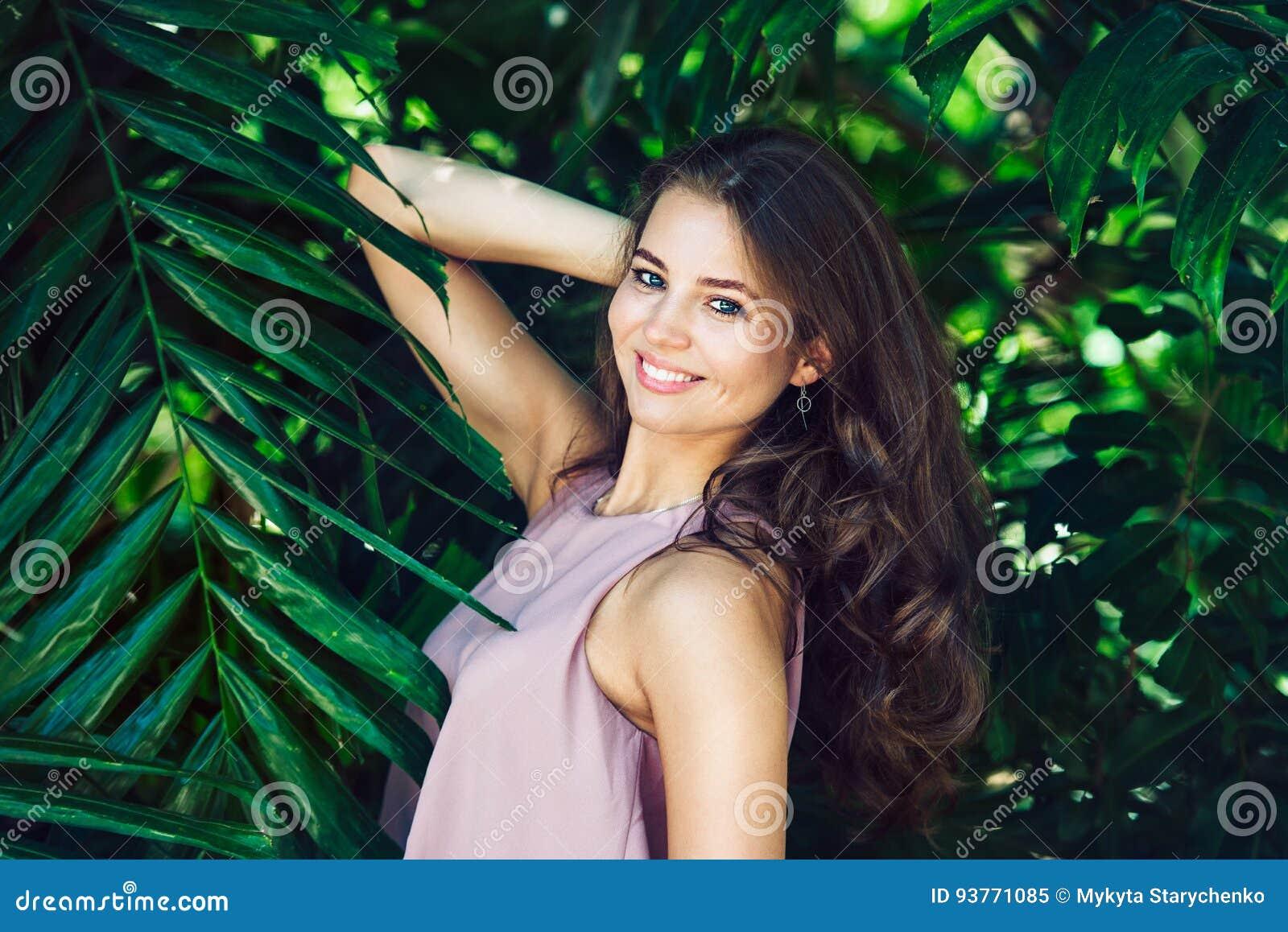 Mujer sonriente hermosa que presenta en fondo tropical verde natural del bosque