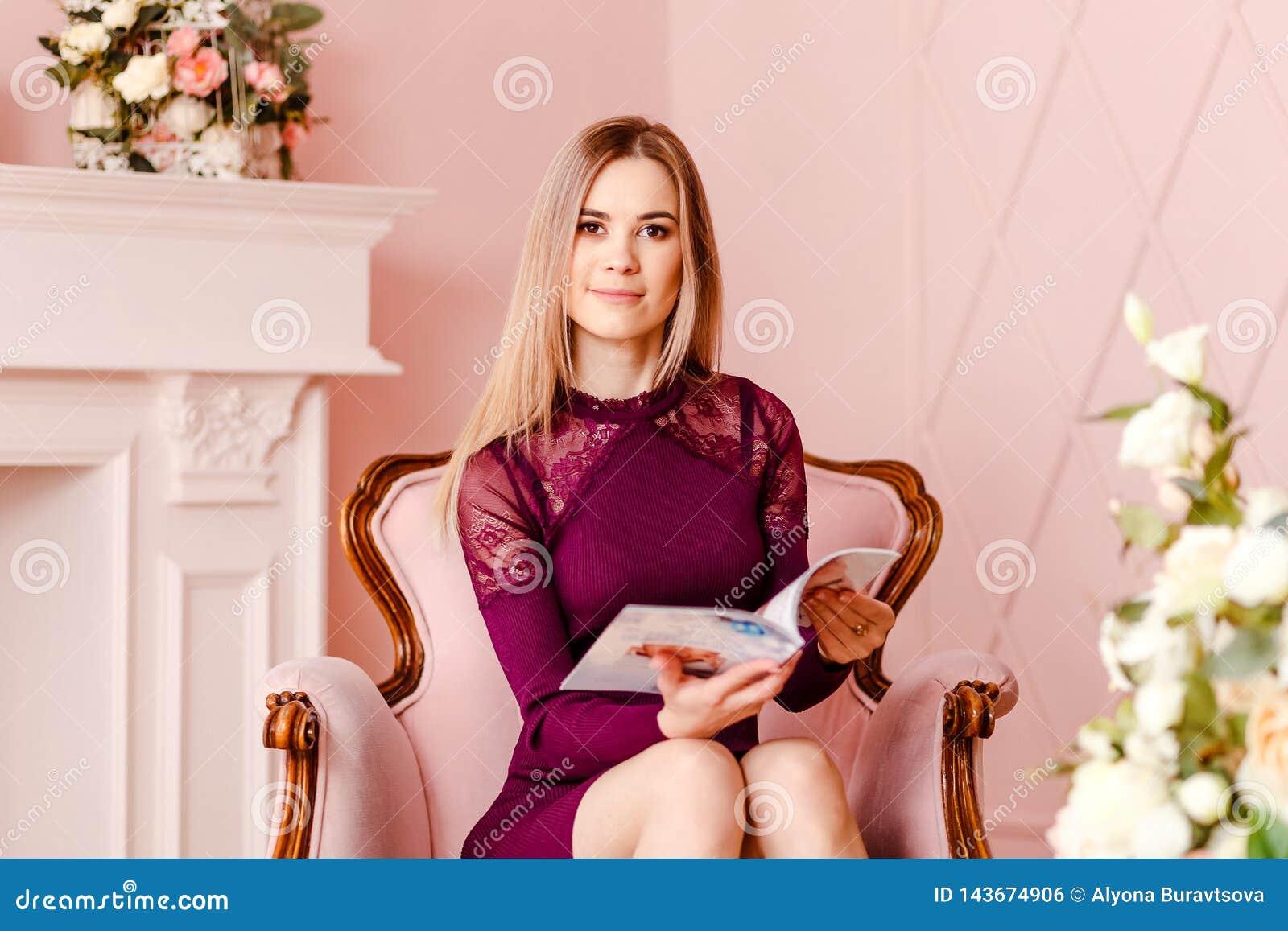 Mujer sonriente hermosa Veinte-año-vieja que se sienta en una silla rosada y que sostiene una revista