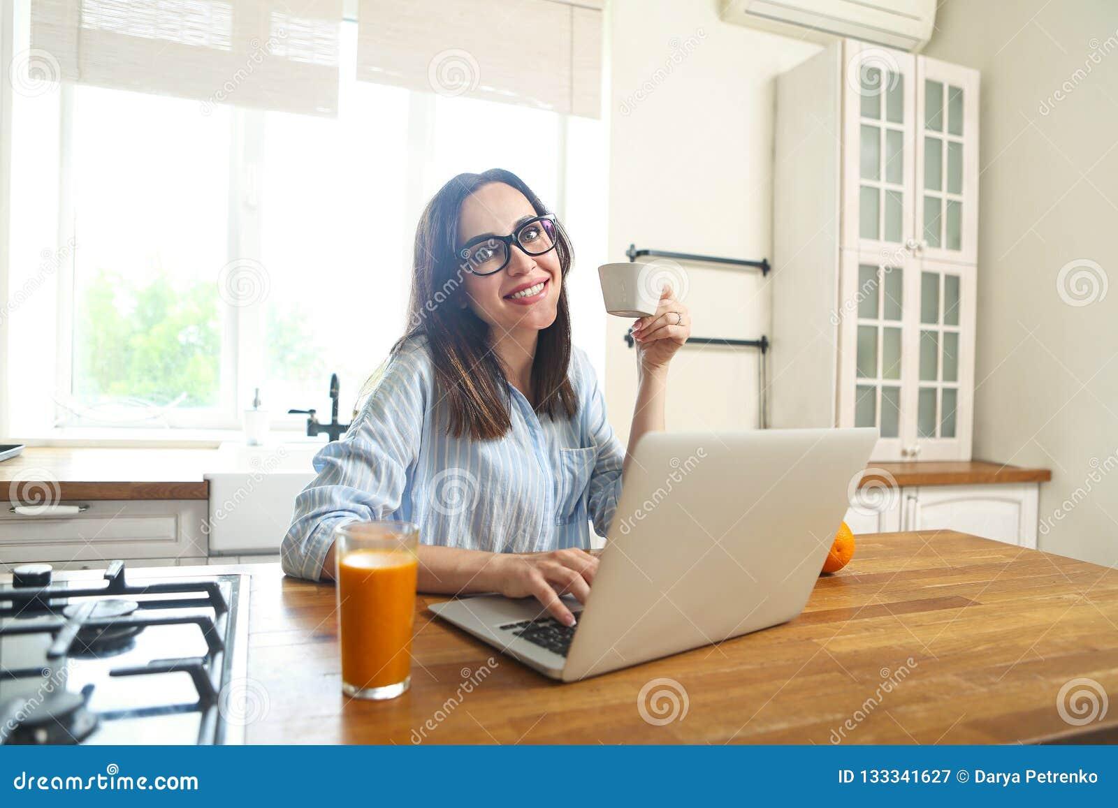 Mujer sonriente joven con el ordenador y la taza de café en el kitch