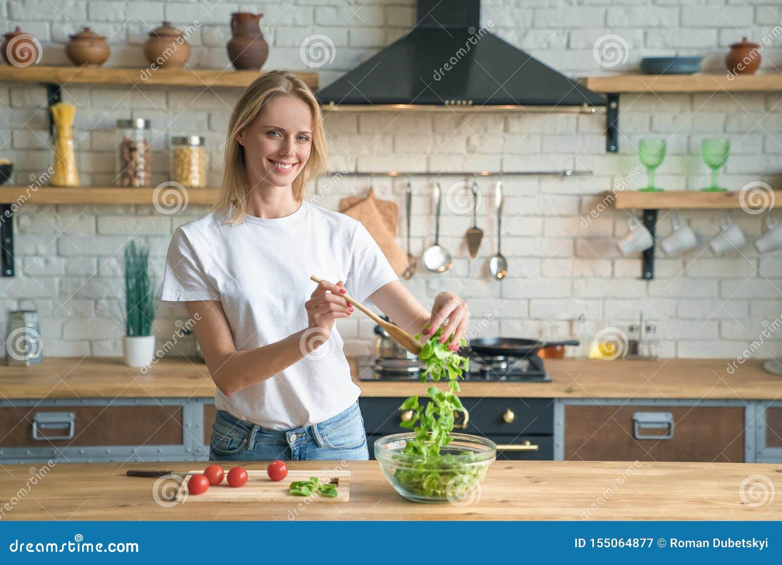 Mujer sonriente joven hermosa que hace la ensalada en la cocina Alimento sano Ensalada vegetal Dieta Forma de vida sana El cocina