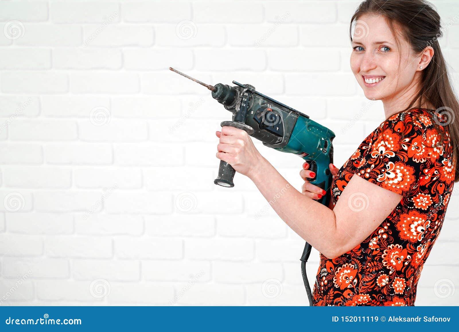 Mujer sonriente joven que presenta con el martillo