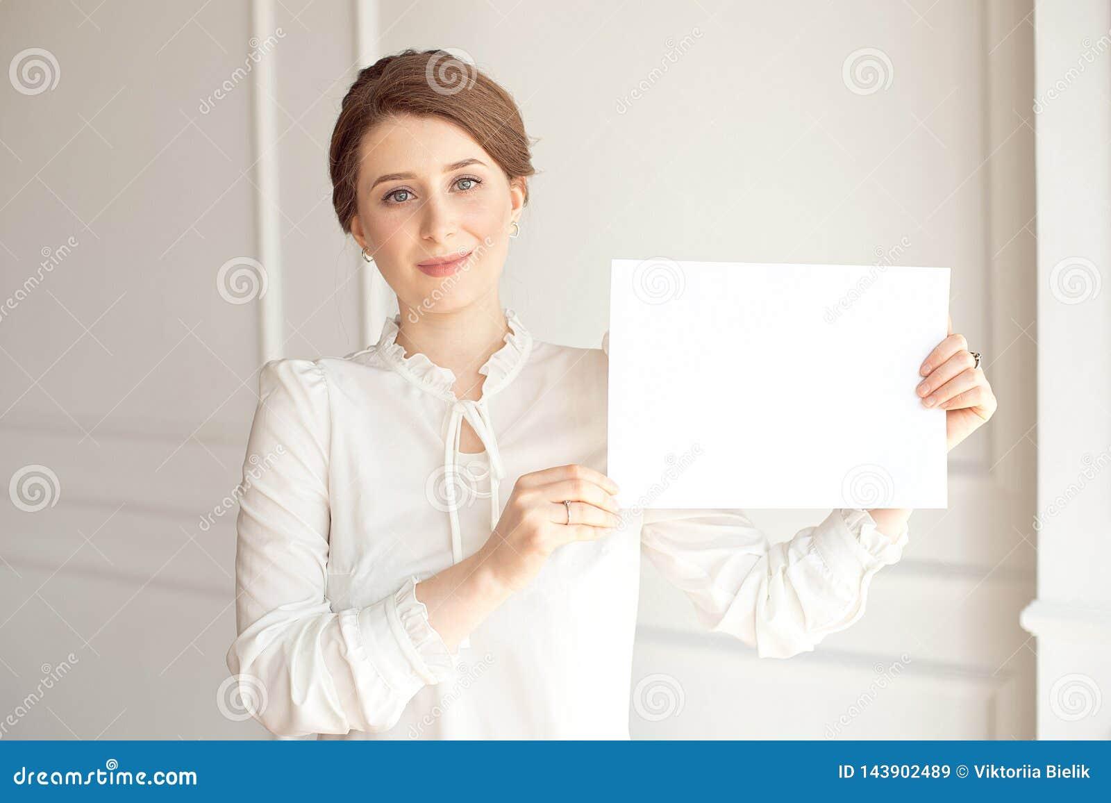 Mujer sonriente joven que sostiene una hoja de papel en blanco para hacer publicidad Muchacha que muestra la bandera con el espac