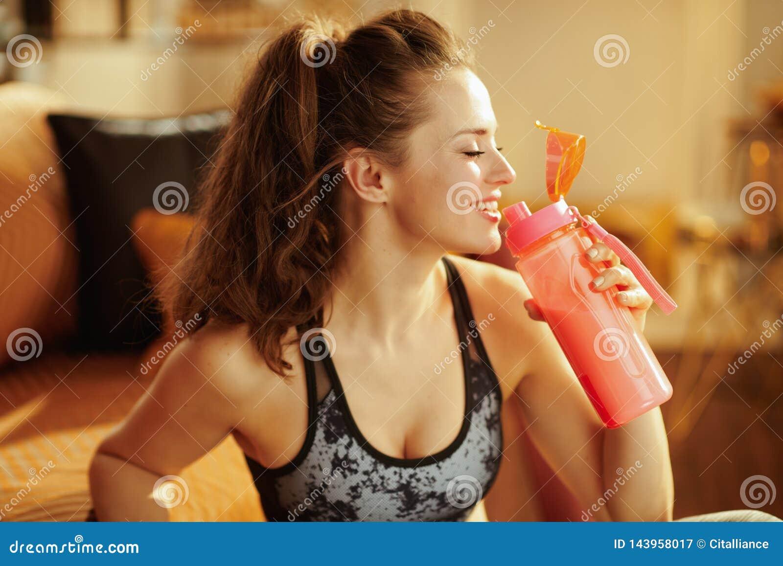 Mujer sonriente que bebe de la coctelera con suplementos de la proteína