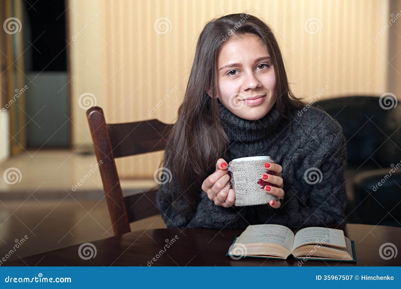 Mujer sonriente que bebe el té delicioso que se sienta en la tabla