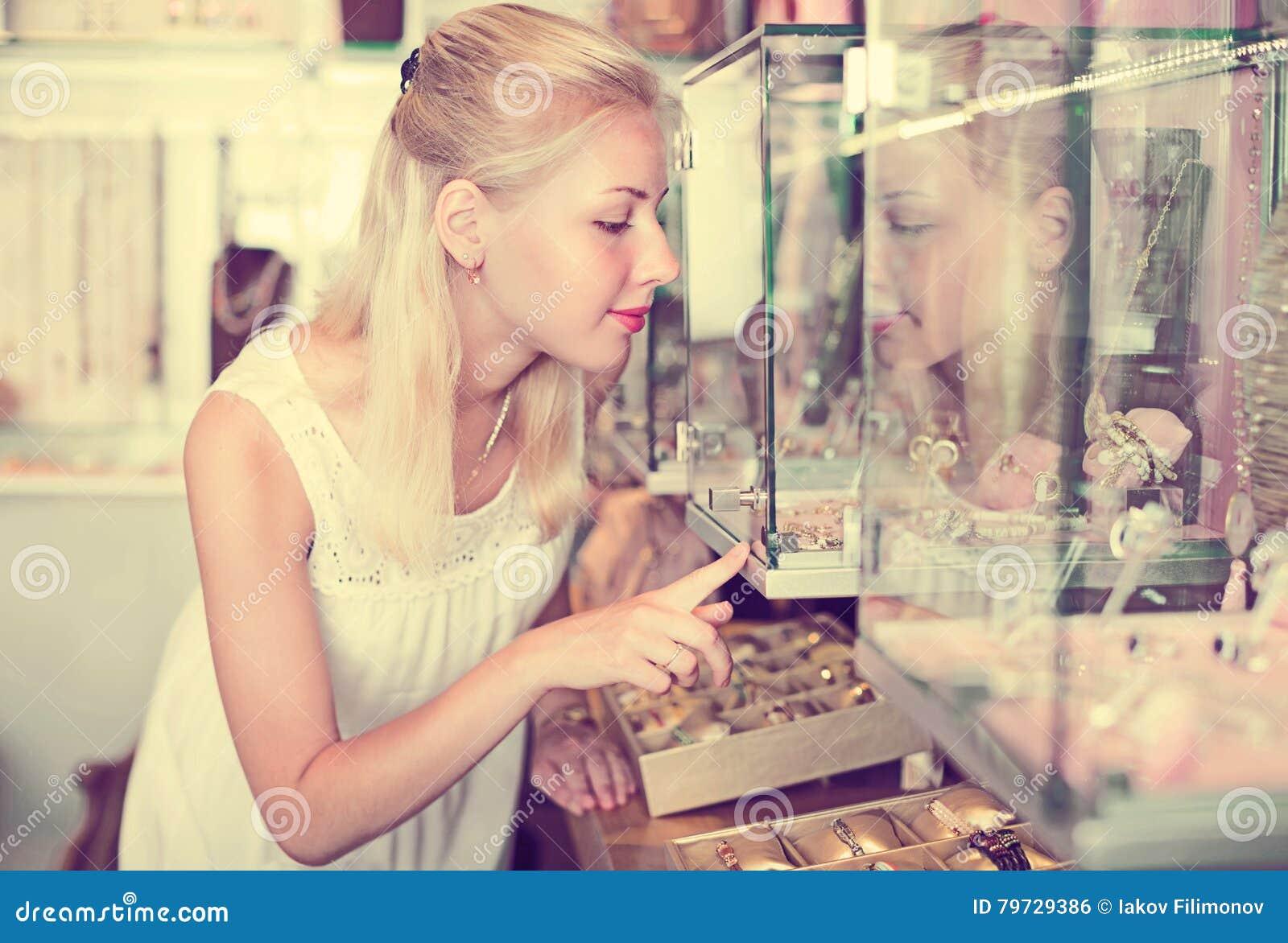 Mujer sonriente que elige el bijouterie en el escaparate de cristal