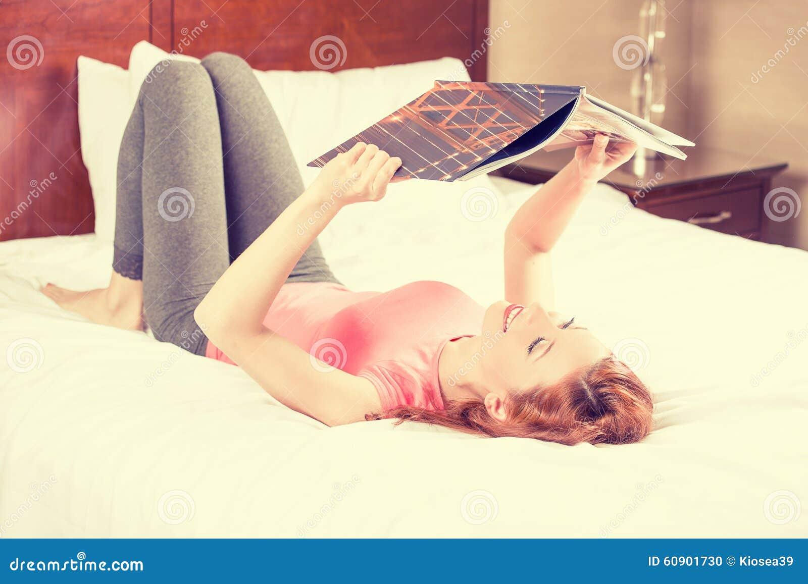 Mujer sonriente que miente en cama mientras que lee una revista, guía del viaje