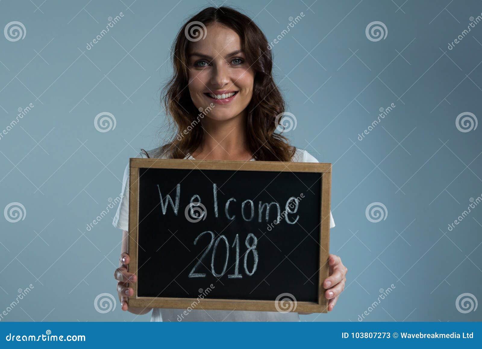 Mujer sonriente que muestra la pizarra con la recepción 2018 del texto contra fondo gris