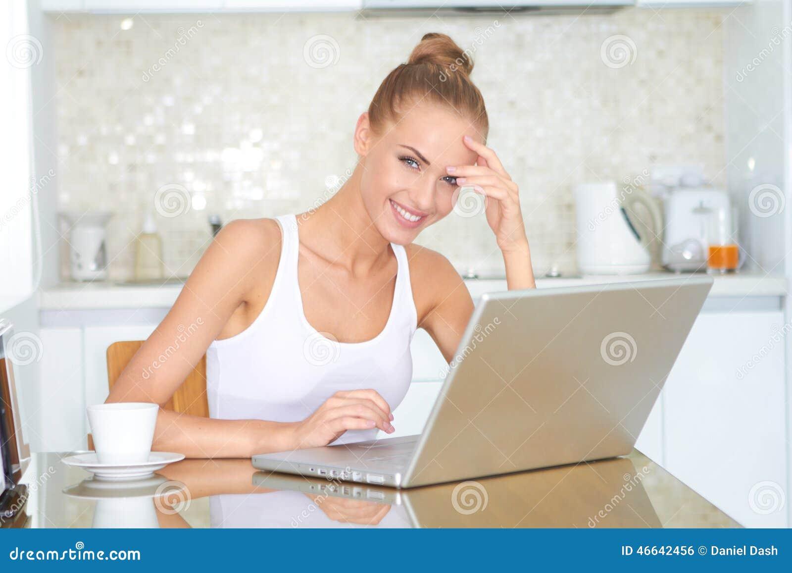 Mujer sonriente que trabaja en un ordenador portátil en casa