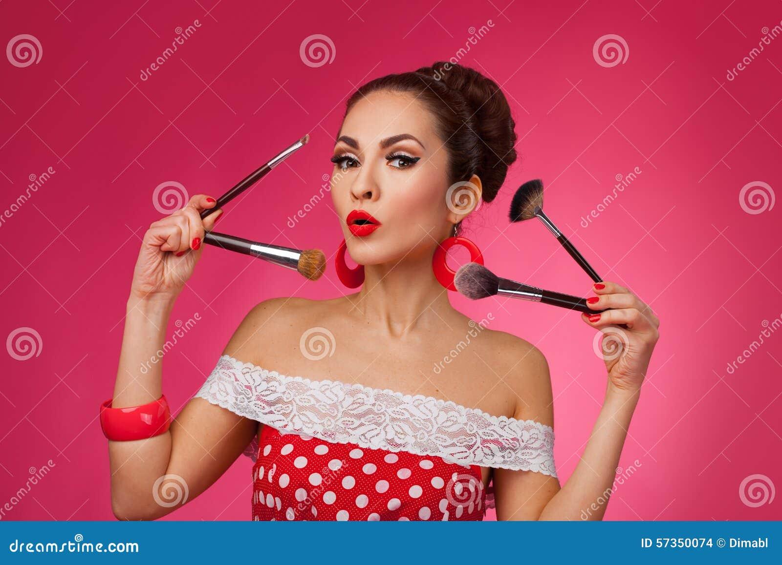 Mujer sorprendida con los cepillos del maquillaje Ella es