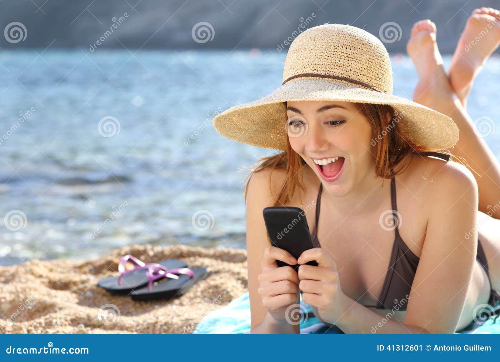 Mujer sorprendida divertida que mira medios sociales en un teléfono elegante en la playa