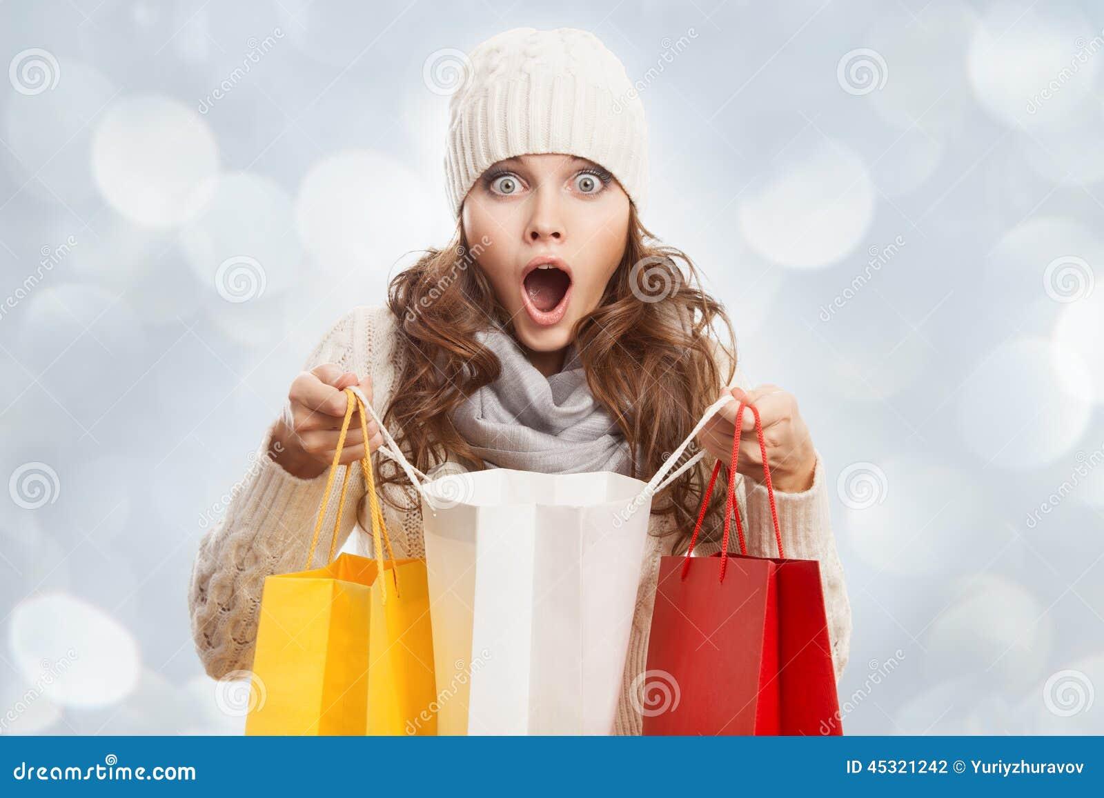 Mujer sorprendida que hace compras que sostiene bolsos Ventas del invierno