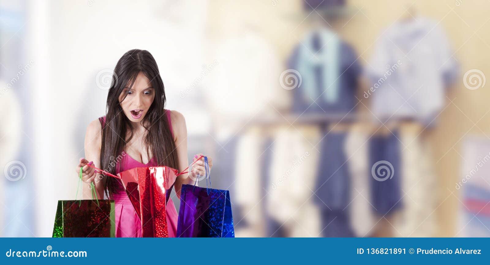 Mujer sorprendida que mira compras