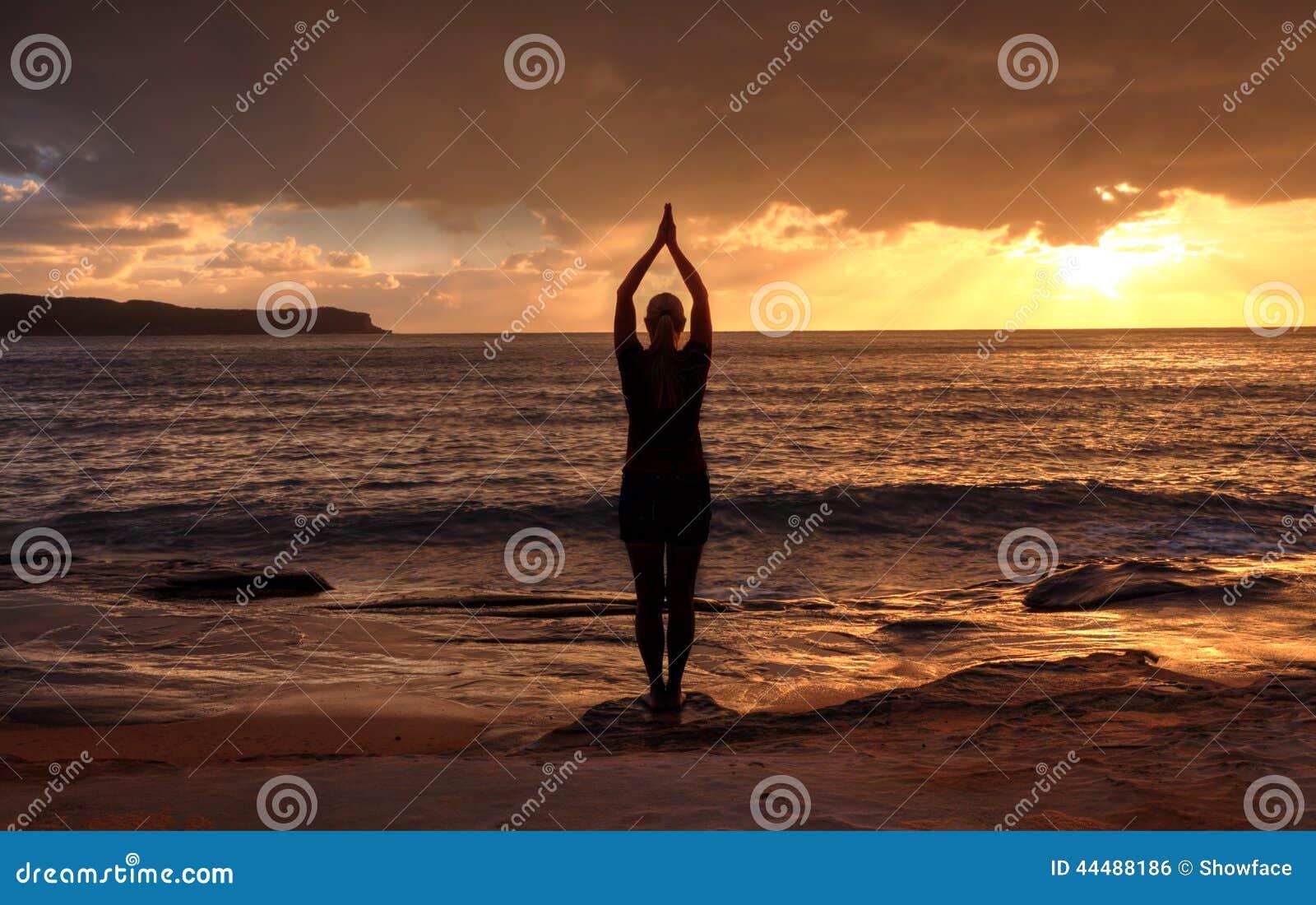 Mujer Tadasana - yoga de la actitud de la montaña por el mar en la salida del sol