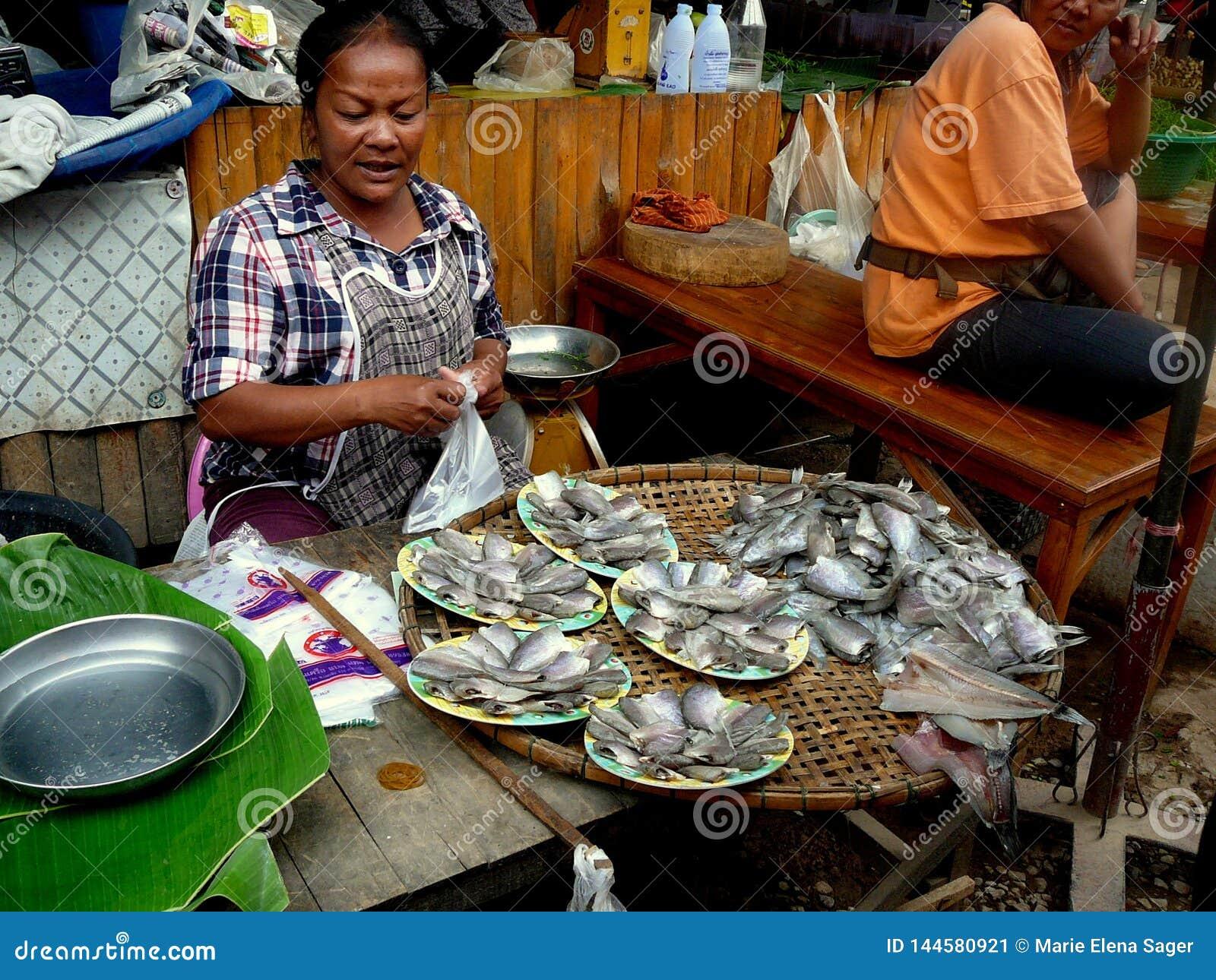 Mujer tailandesa que vende pescados en el mercado de la madrugada
