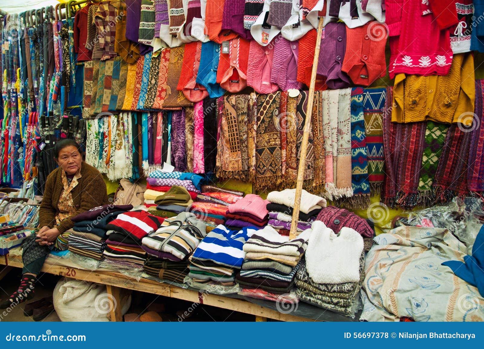 Mujer tibetana que vende la ropa de lana