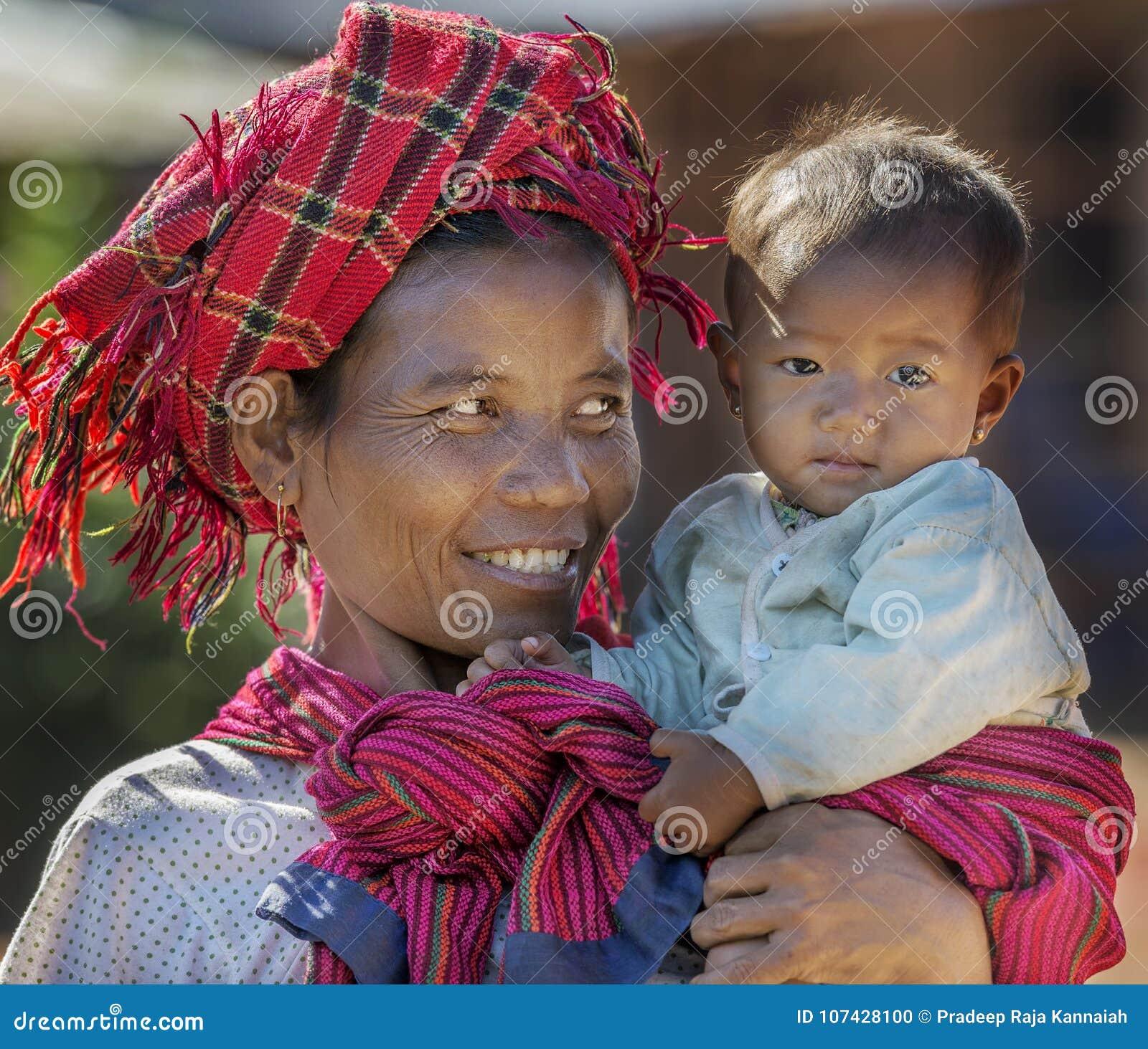 Mujer tribal de Intha que detiene a su niño en su brazo feliz, Inle Myanmar