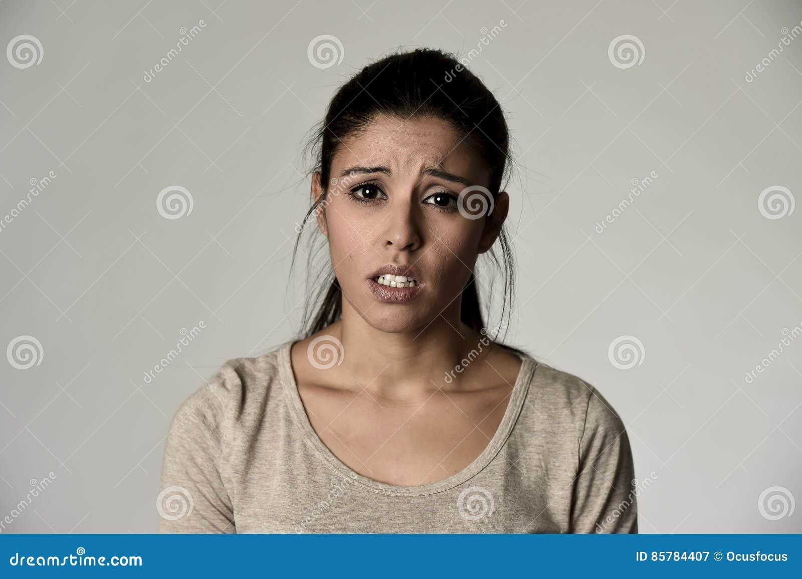 Mujer triste hispánica hermosa joven seria y en cuestión en la expresión facial deprimida preocupante