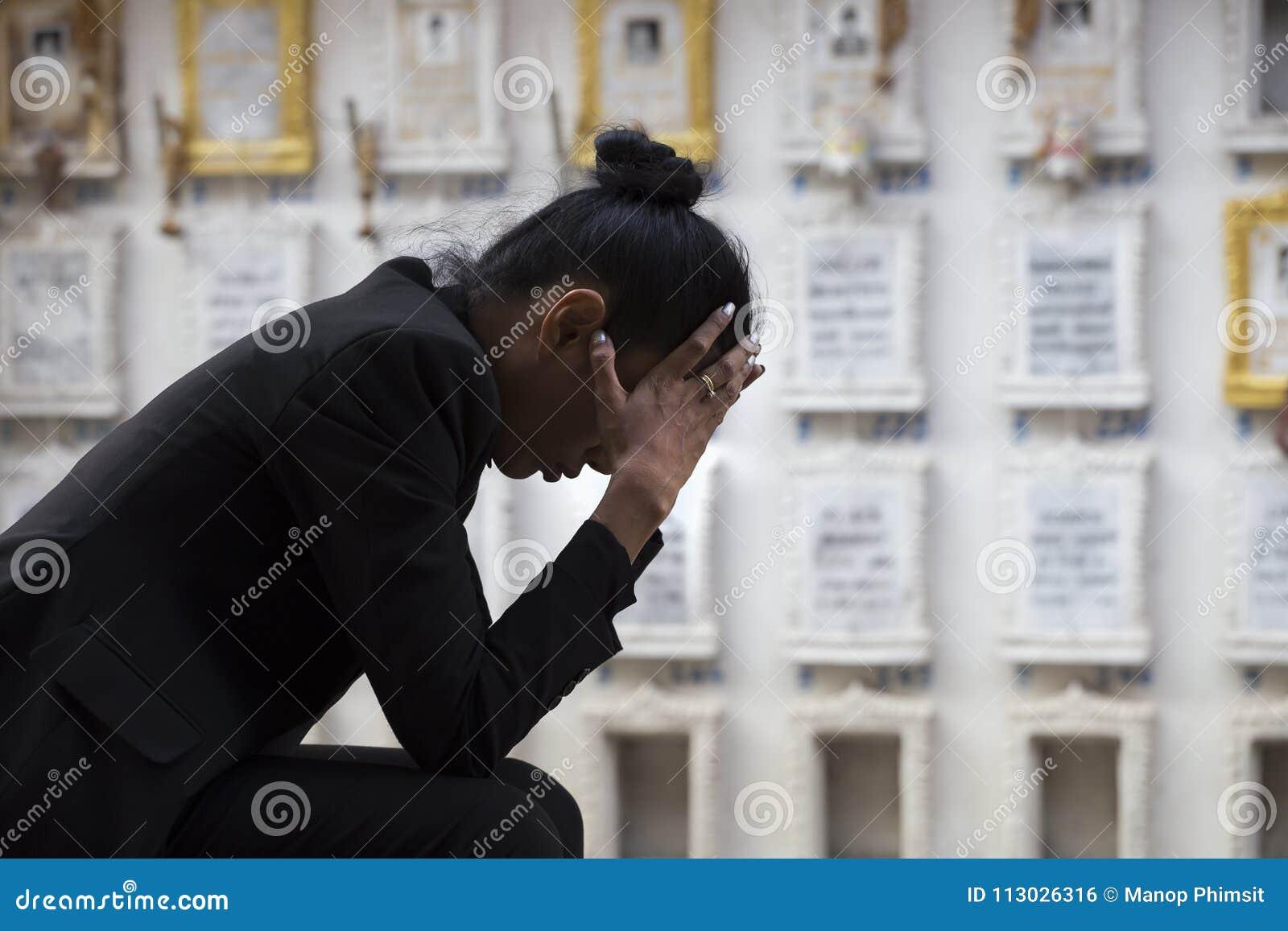 Mujer triste que se sienta cerca de un sepulcro