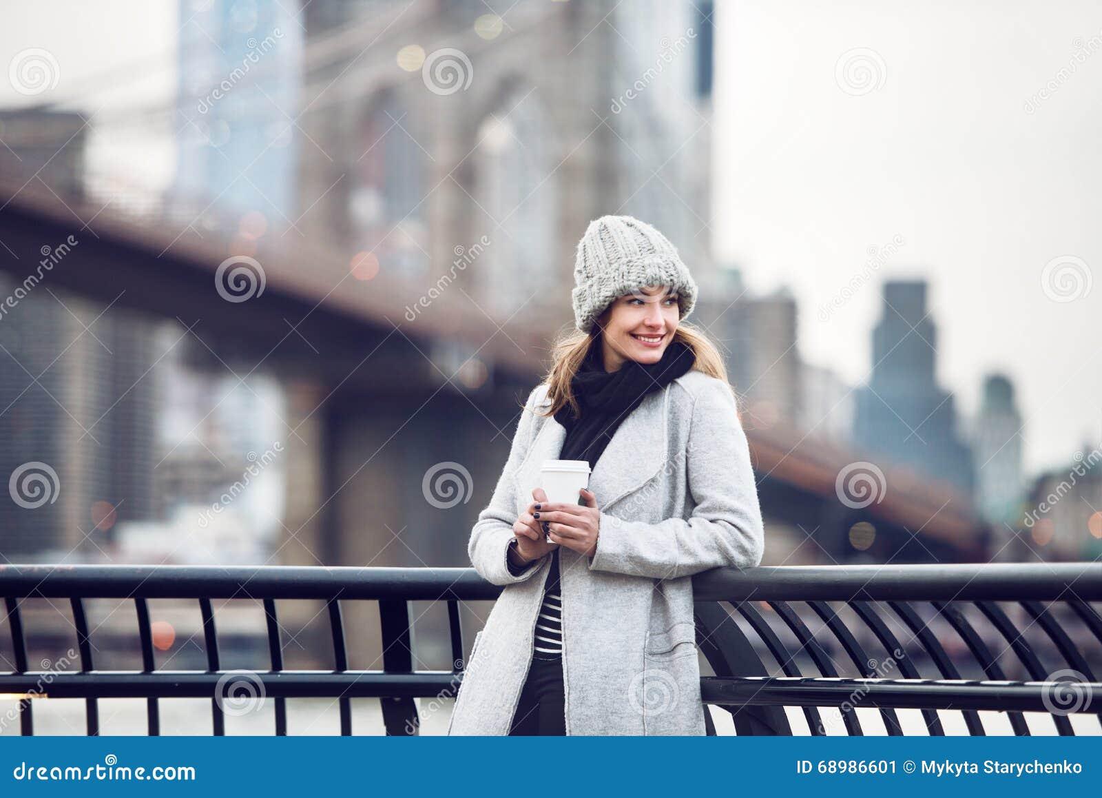 Mujer turística adulta sonriente feliz que sostiene la taza de café de papel y que disfruta de la opinión de New York City