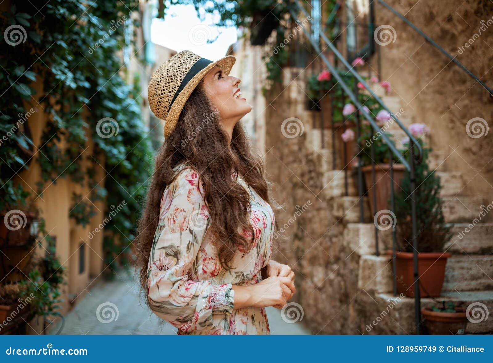 Mujer turística moderna sonriente en ciudad italiana vieja que hace turismo
