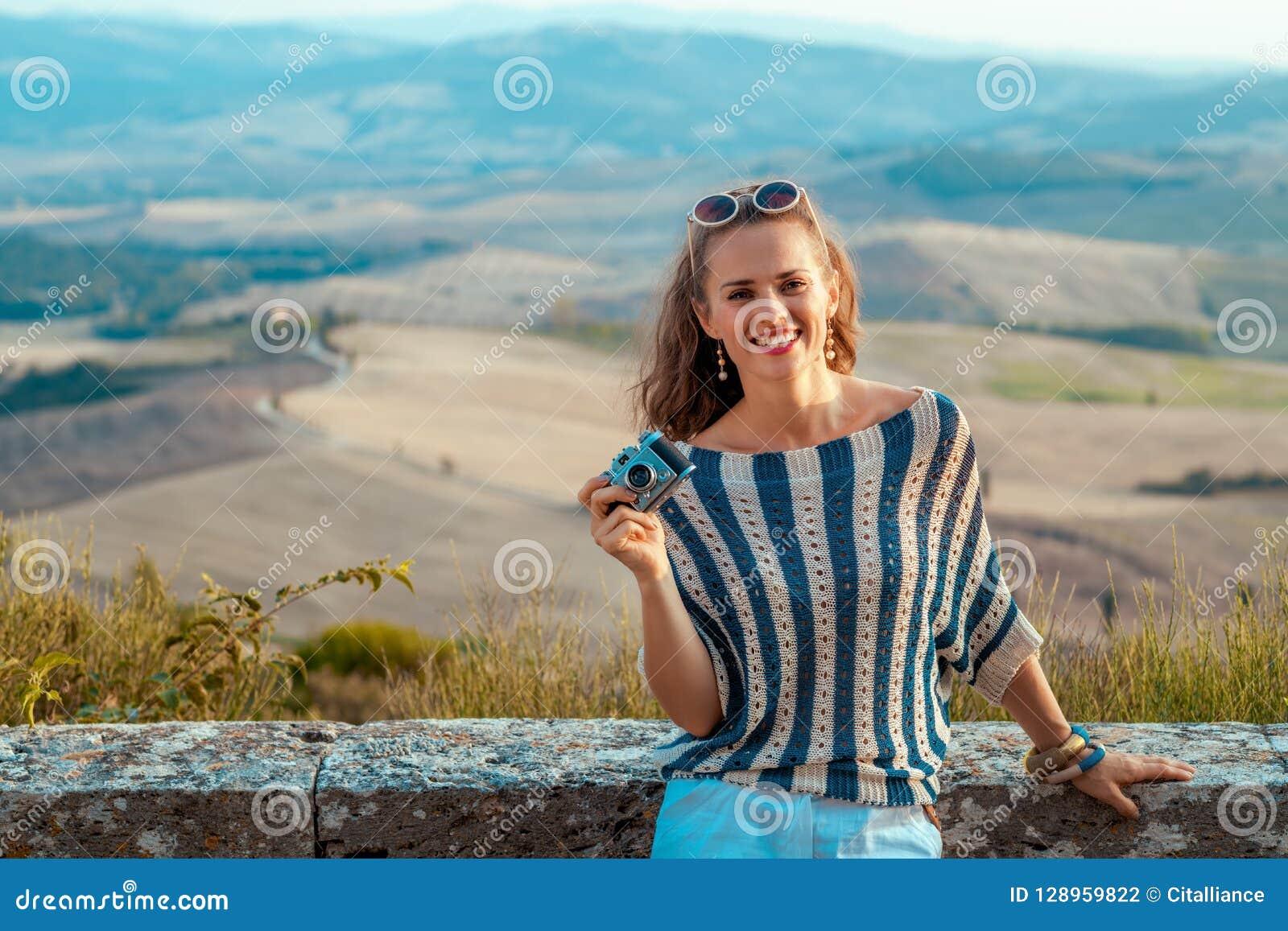 Mujer turística sonriente con la cámara retra de la foto en Toscana