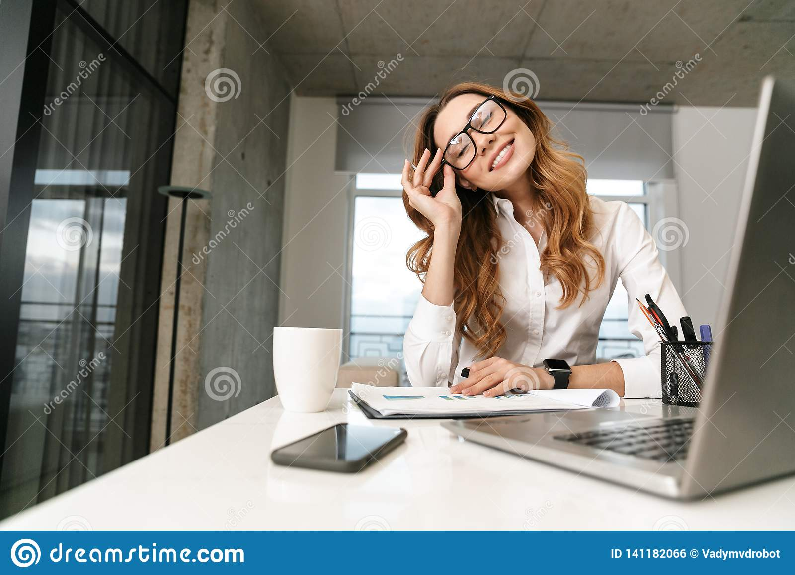 Mujer vestida en camisa formal de la ropa dentro usando el ordenador portátil