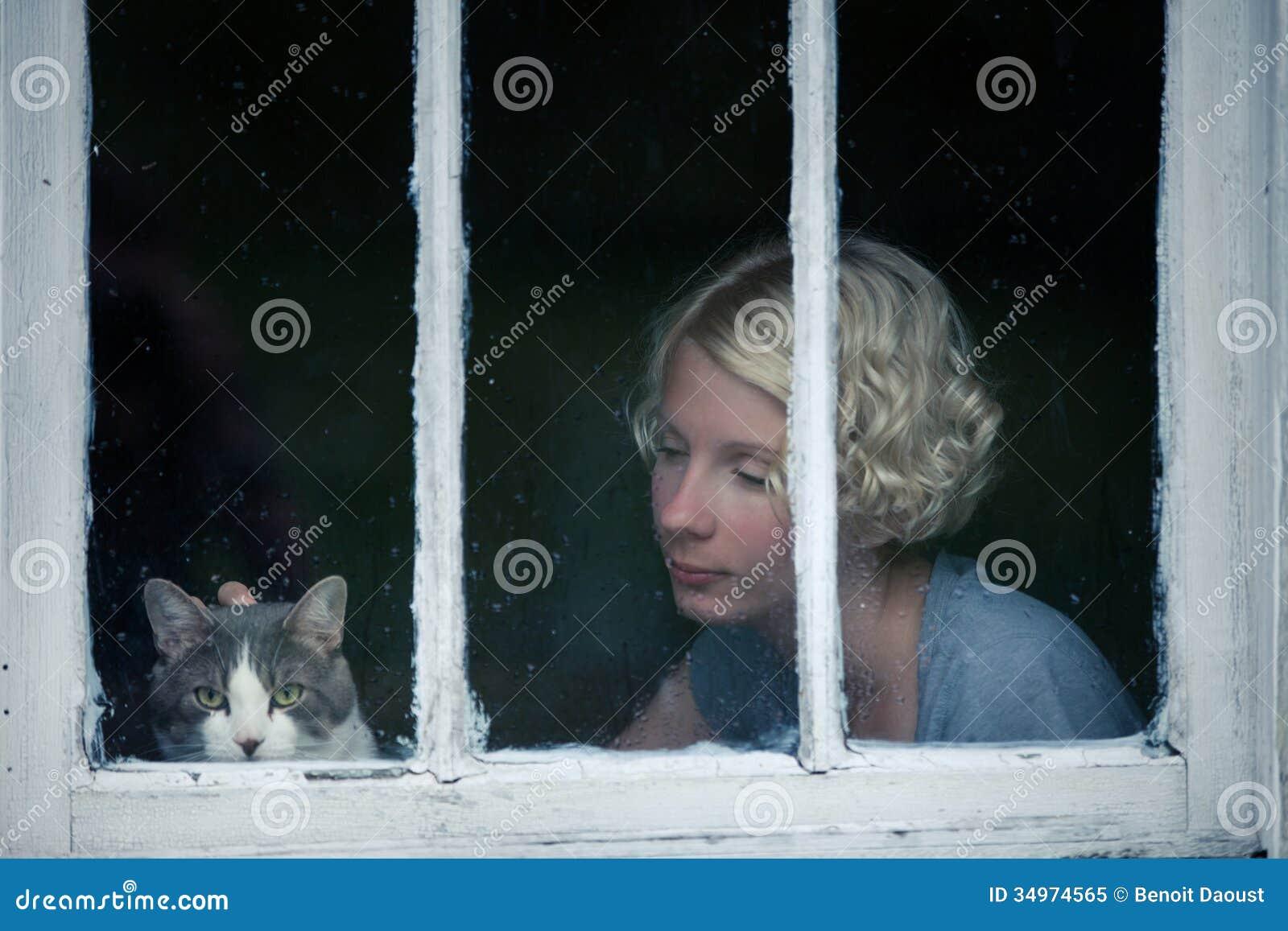 Mujer y Cat Looking en el tiempo lluvioso por la ventana